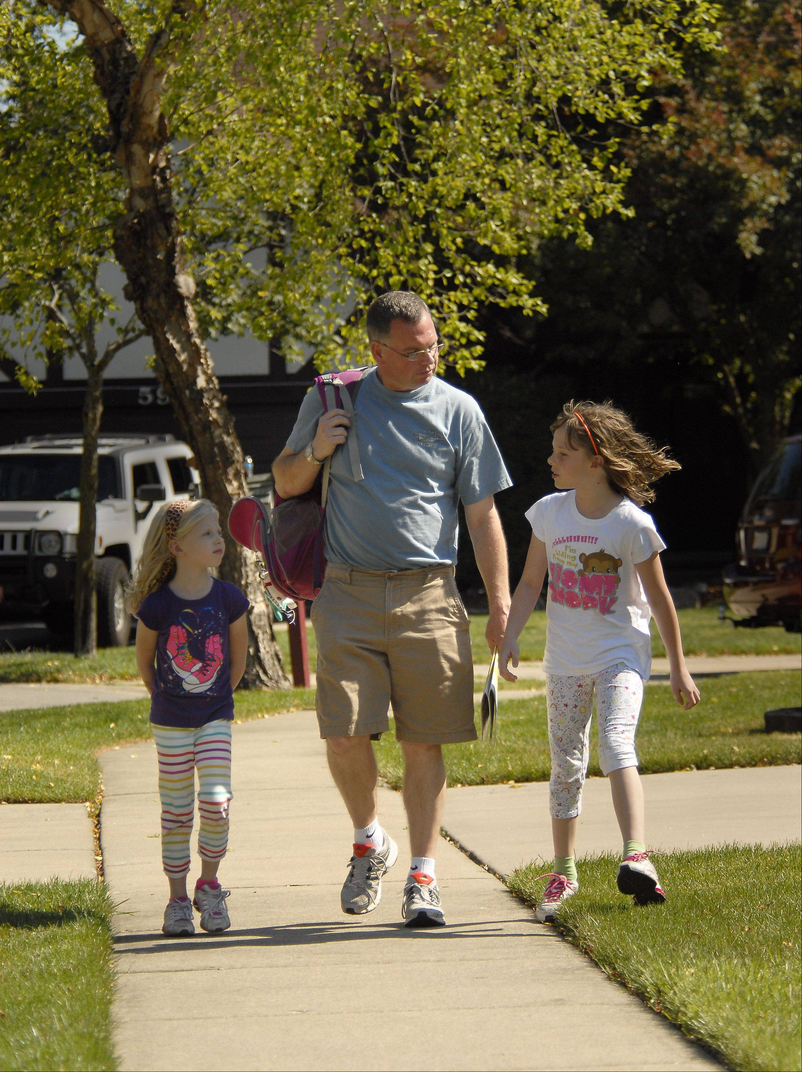 Stay-at-home dad Randy Reid walks his daughters Maddie, 6, left, and Bella, 8, home from the bus stop.