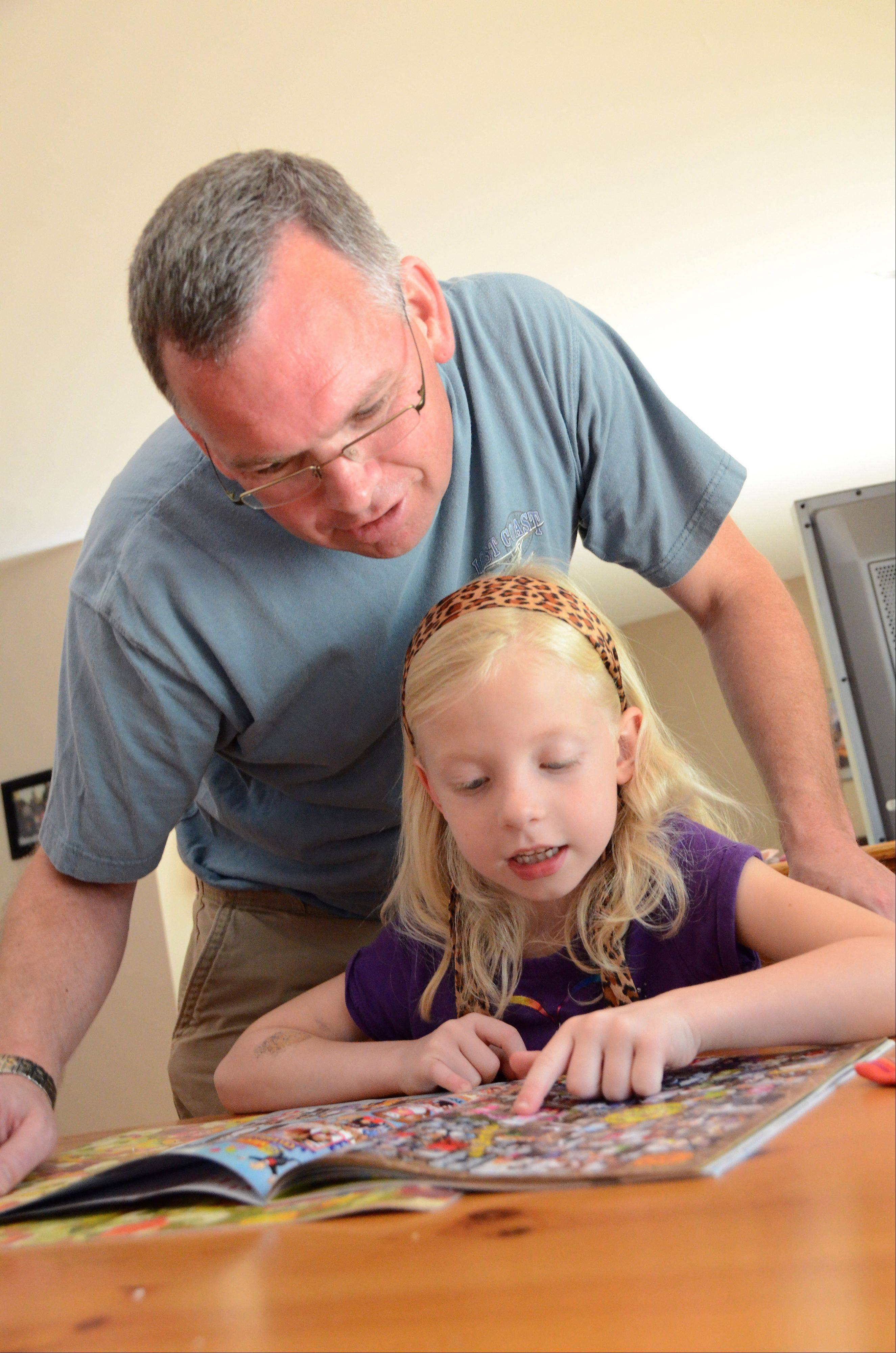 Stay-at-home dad Randy Reid looks at the yearbook his daughter Maddie, 6, after school.
