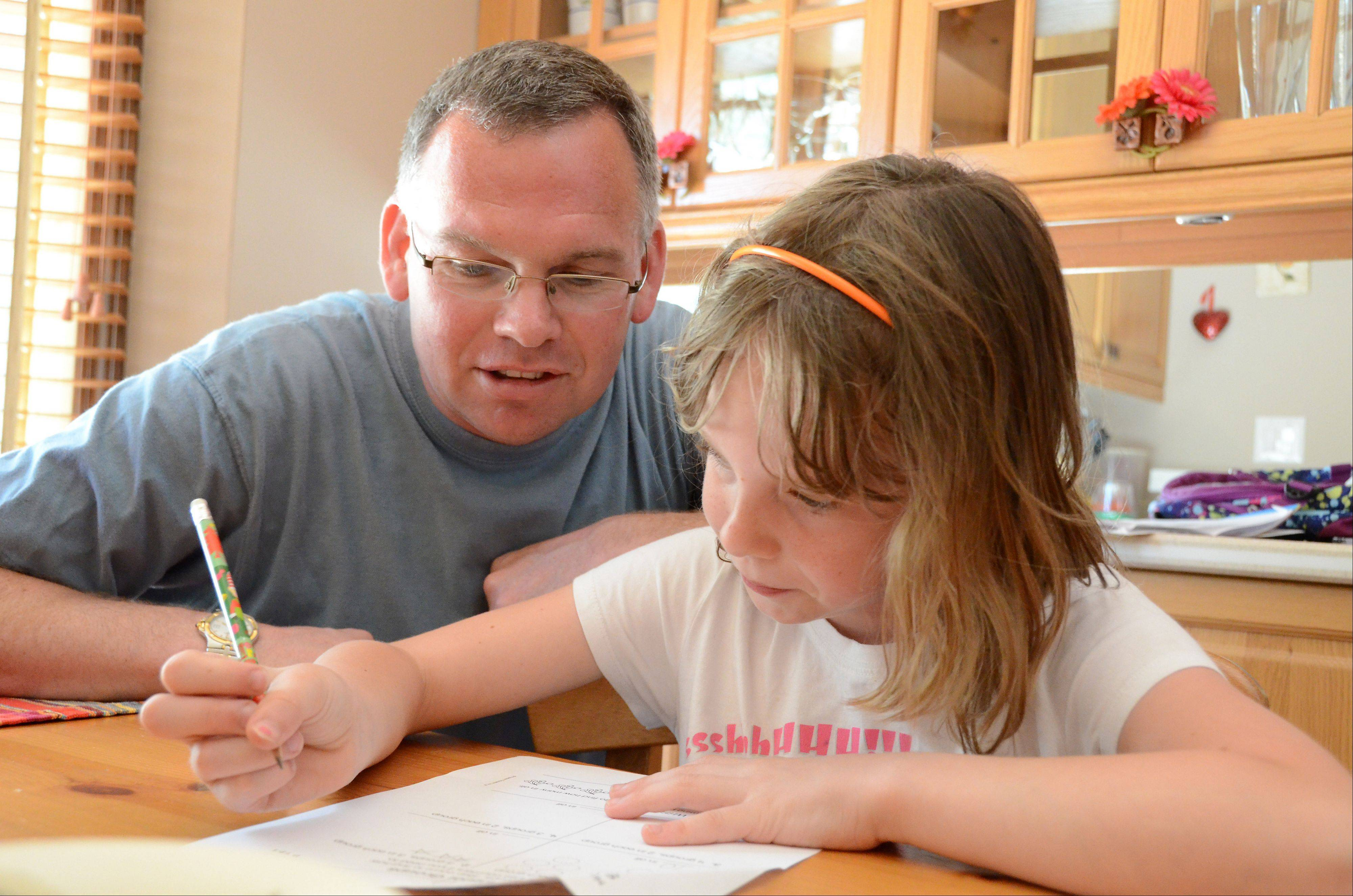 Stay-at-home dad Randy Reid works with his daughter Bella, 8, as she does her homework after school.