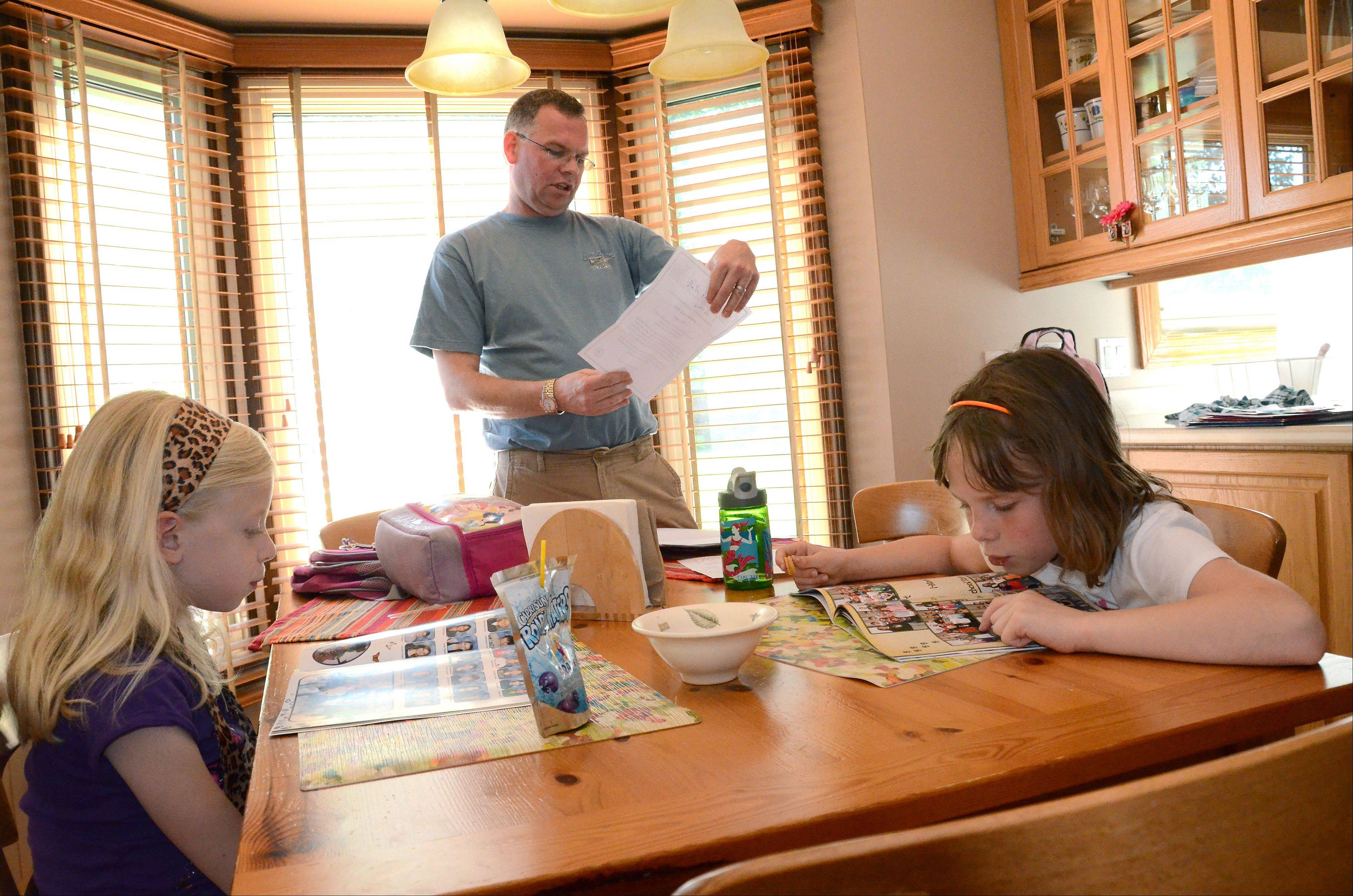 Randy Reid checks homework and such in the backpacks of his daughters Maddie, 6, left, and Bella, 8, after they get home from school.