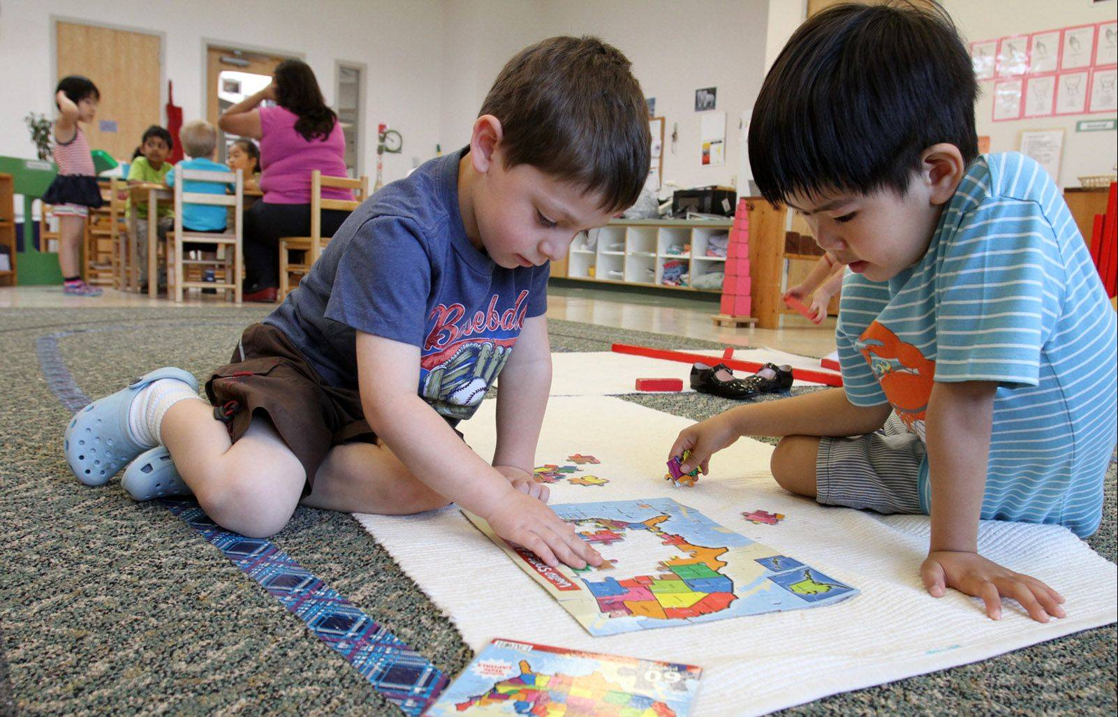 Rahm Sheinfeld, 4, left, and Alex Seo, 5, work on the U.S. map puzzle at the Montessori school in Wheeling. The Montessori school works with children from newborns to 12-year-olds.