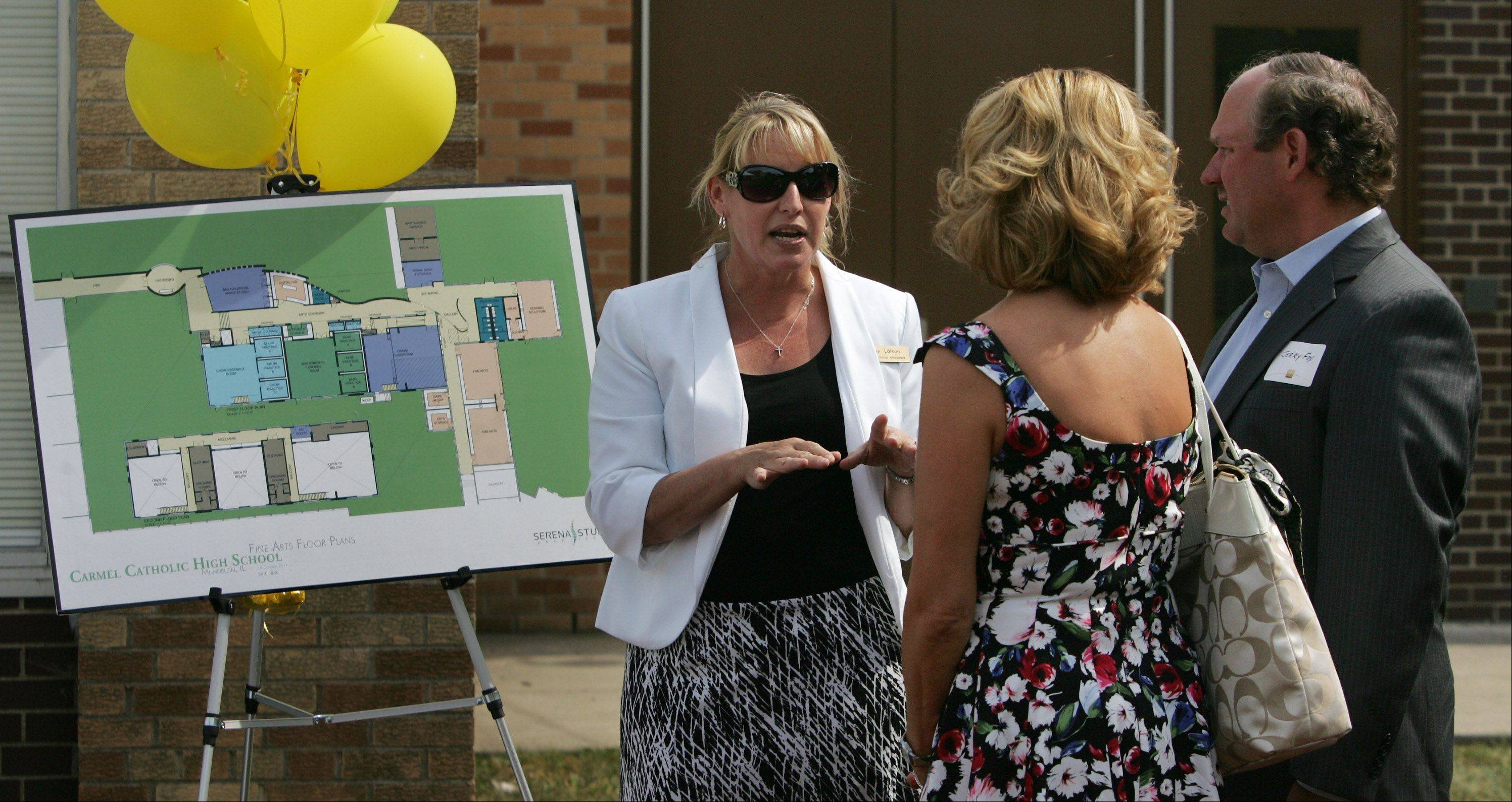 Volunteer Betsy Larson, of Gurnee, talks to Caryn and Jerry Fox, of Hawthorn Woods, about the new Fine Arts facility before the groundbreaking ceremony Thursday at Carmel Catholic High School. The arts center will include a dance studio, a black box theater, art gallery space and more.