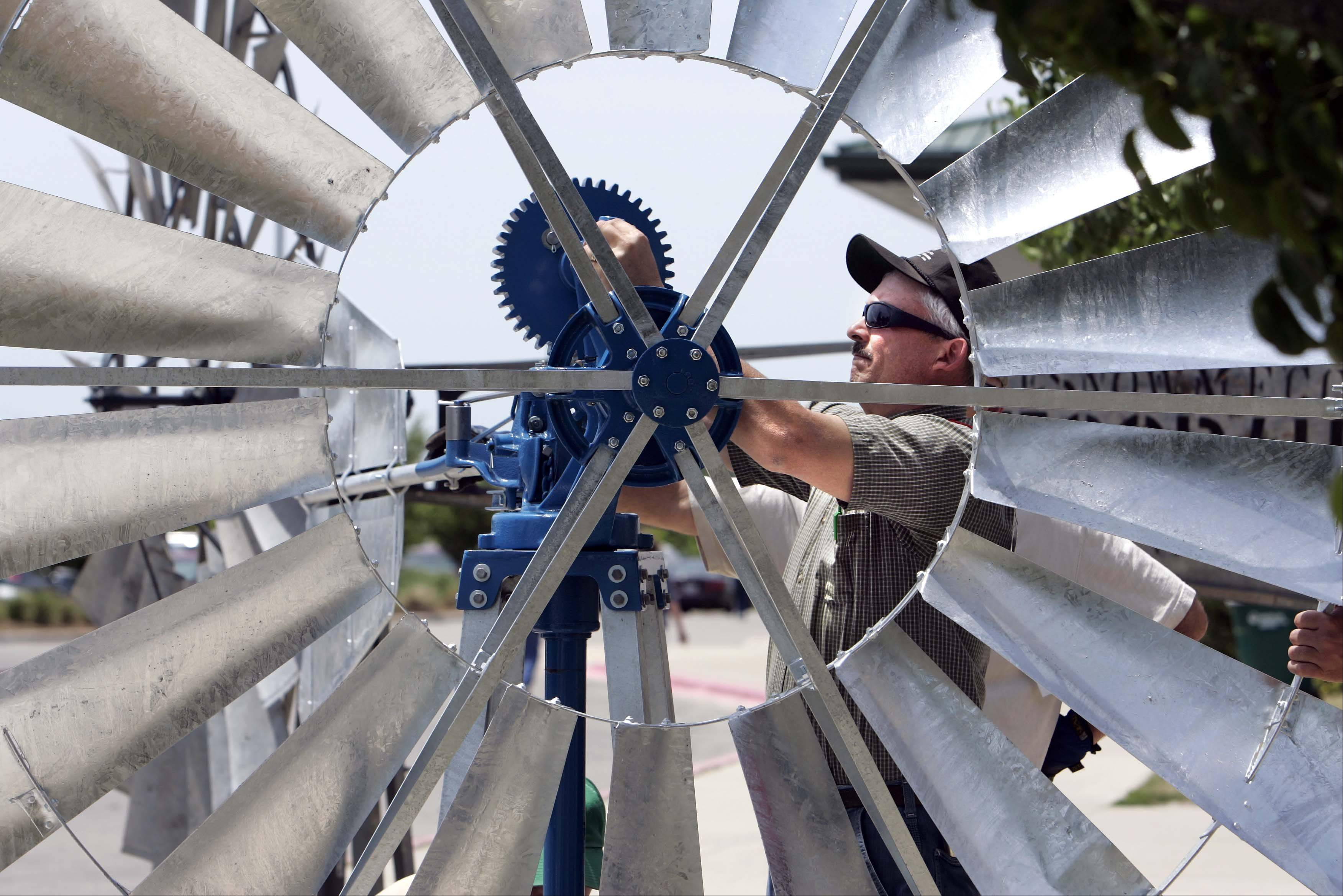 "Todd Skinner of Churubusco, Ind., repaired the ""Comet"" a galvanized steel wind engine that is on display during the 24th annual International Windmillers' Trade Fair going on through Saturday at Batavia High School. Windmill enthusiasts from all over the globe will be in attendance to celebrate their love for windmills. Batavia was once known as the windmill capital of the world."