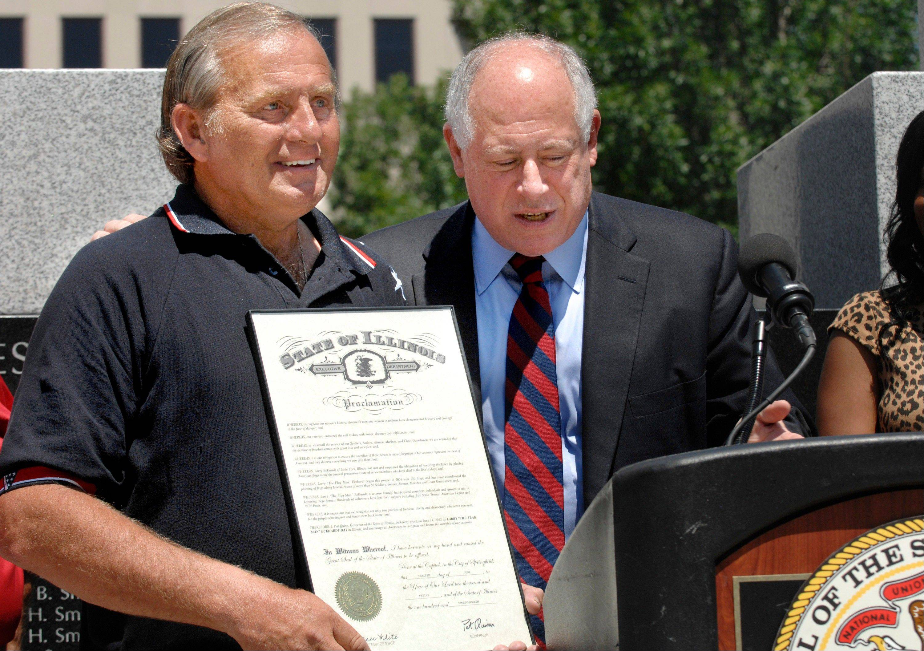 "Larry ""The Flagman"" Eckhardt, left, holds a proclamation given to him Thursday by Gov. Pat Quinn in a Flag Day ceremony in Peoria. Eckhardt has placed flags along funeral procession routes for more than 50 servicemen and women killed in action."
