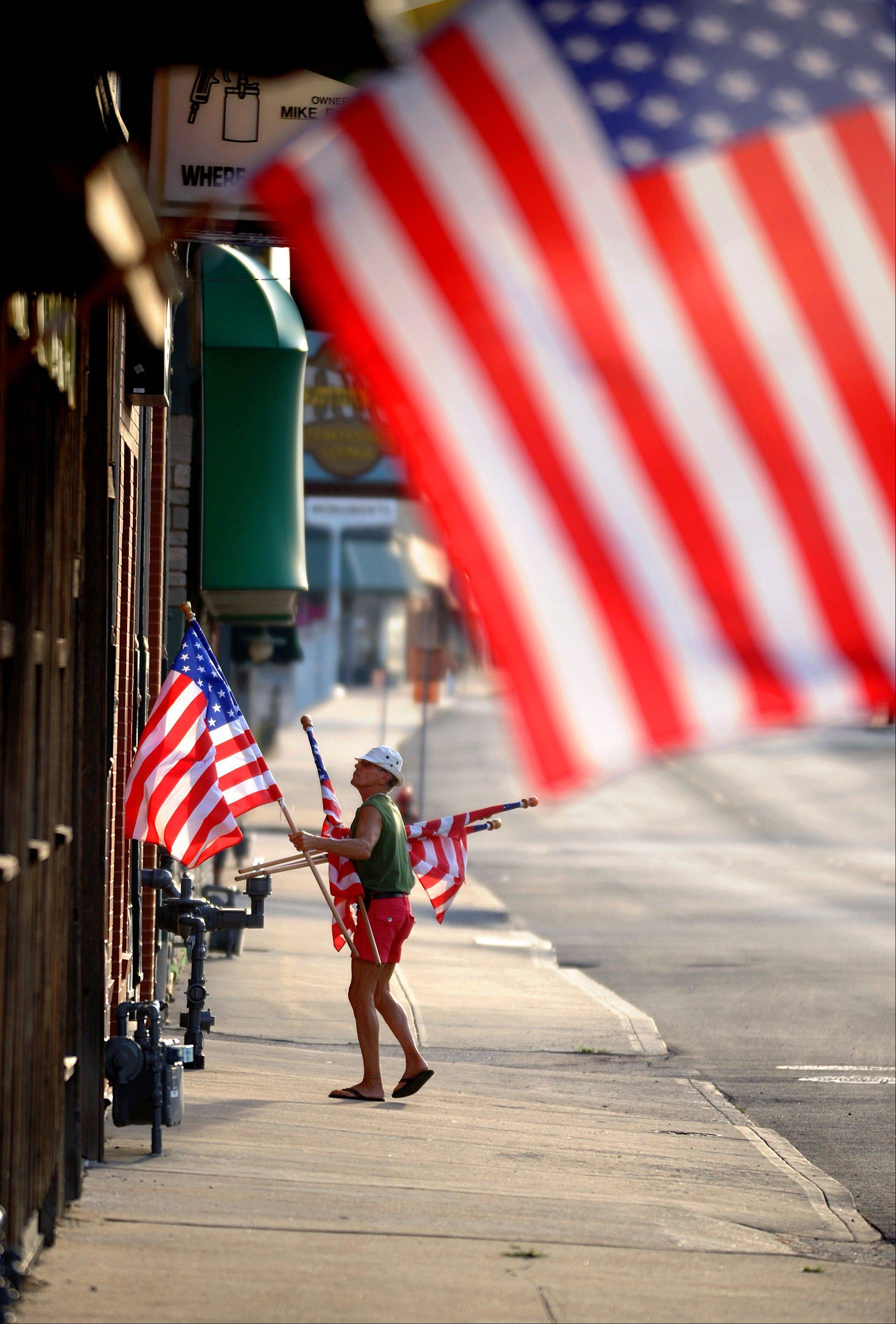 Reid Woodbury places flags along Frederick Avenue in midtown St. Joseph, Mo., on Thursday in honor of Flag Day.