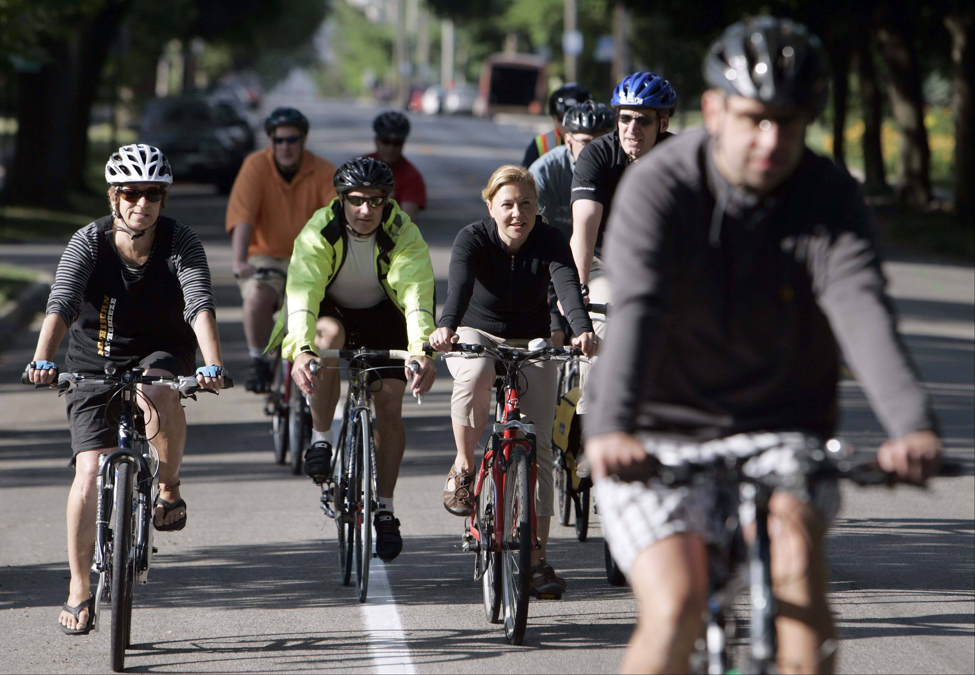 Barb Broeske of Elgin, left, Ron Rudd of West Dundee, Elgin City Councilwoman Anna Moeller of Elgin, and Elgin City Council member John Steffen join the pack during Elgin's Bike To Work Week and breakfast ride Thursday.