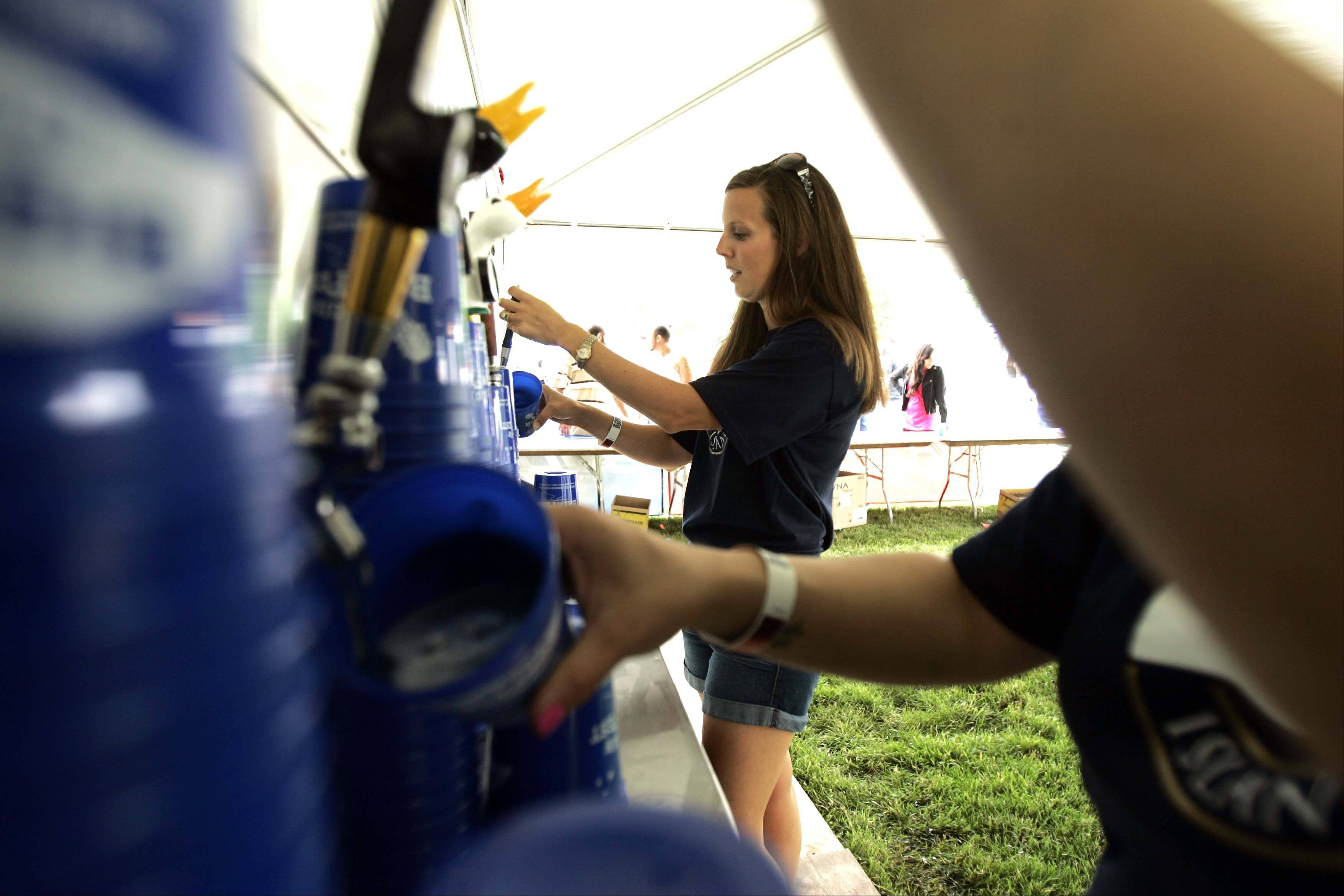 Boys and Girls Club of Elgin volunteer Sonia Lange of Aurora pours a beer during Elgin's annual Brewfest Festival Park. The festival is a fundraiser for the club.