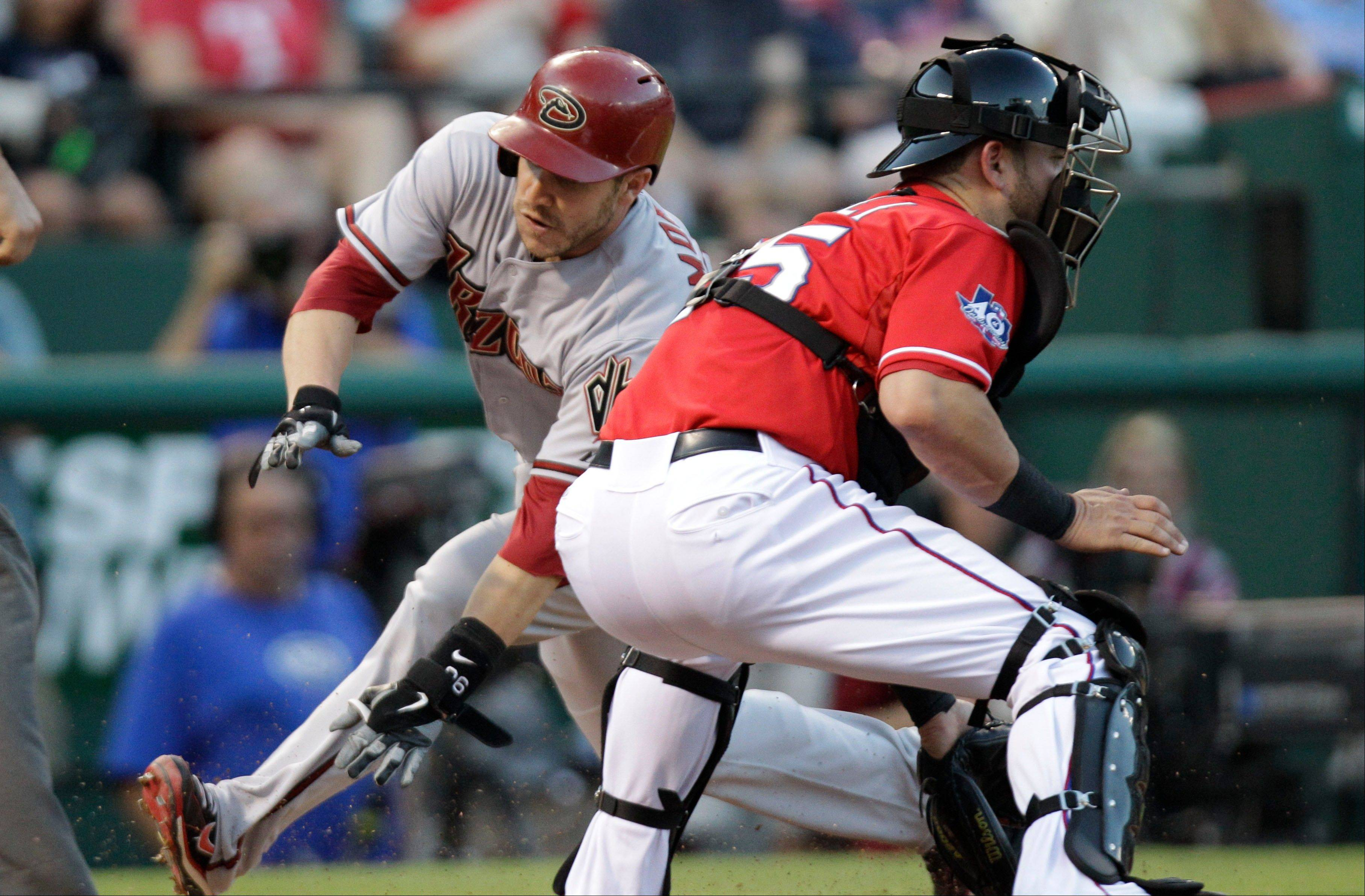 Arizona's Miguel Montero scores before Rangers catcher Mike Napoli gets the ball in the third inning Thursday in Arlington, Texas.