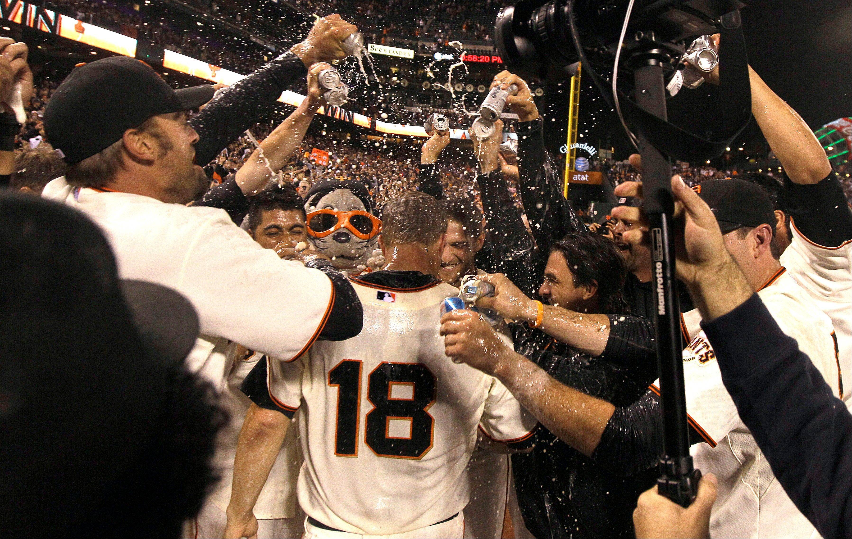 San Francisco Giants pitcher Matt Cain (18) celebrates with teammates Wednesday after throwing a perfect game.
