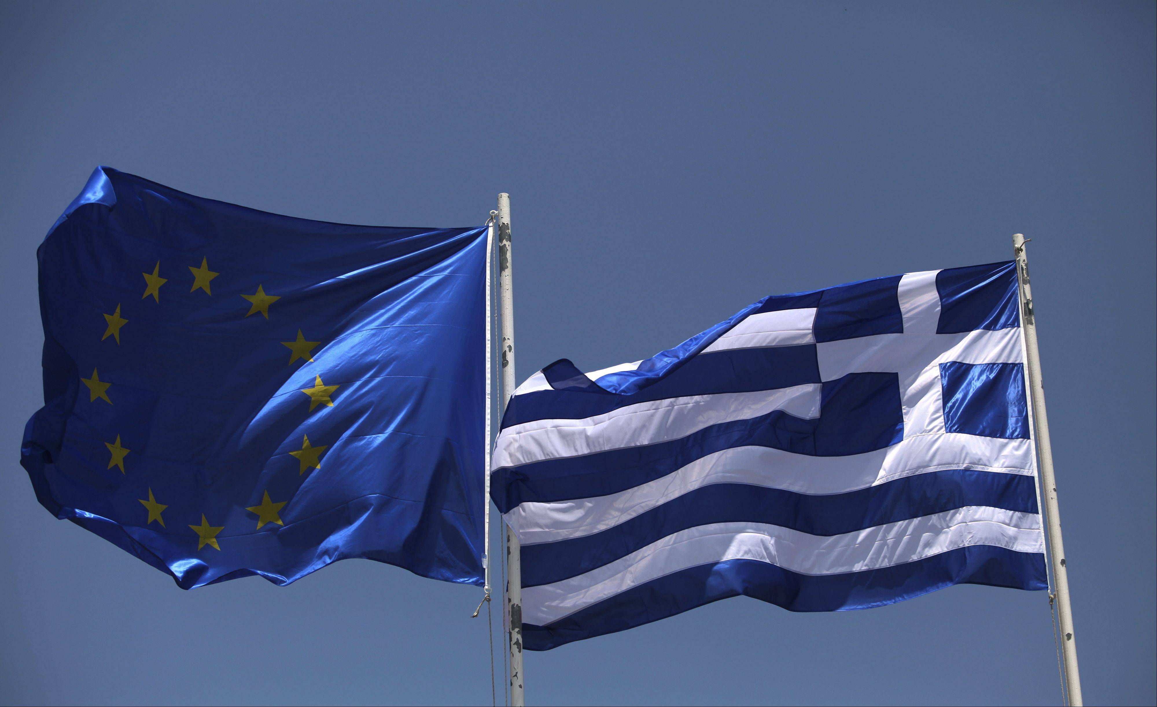 A European Union flag, left, is seen flying alongside a Greek national flag Friday in Athens, Greece.