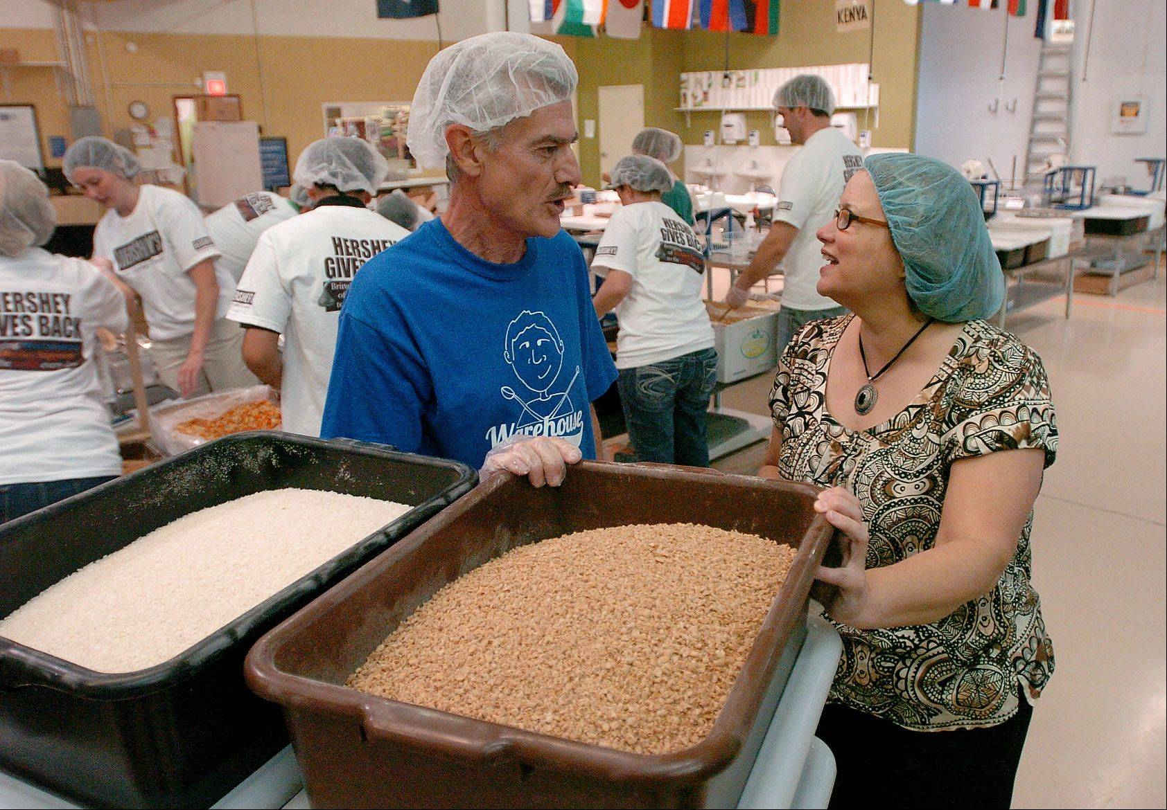 Volunteer Rich Direnzo of Lombard, left, chats with Marilyn Maurella, the Chicagoland development advisor for Feed My Starving Children in Schaumburg.