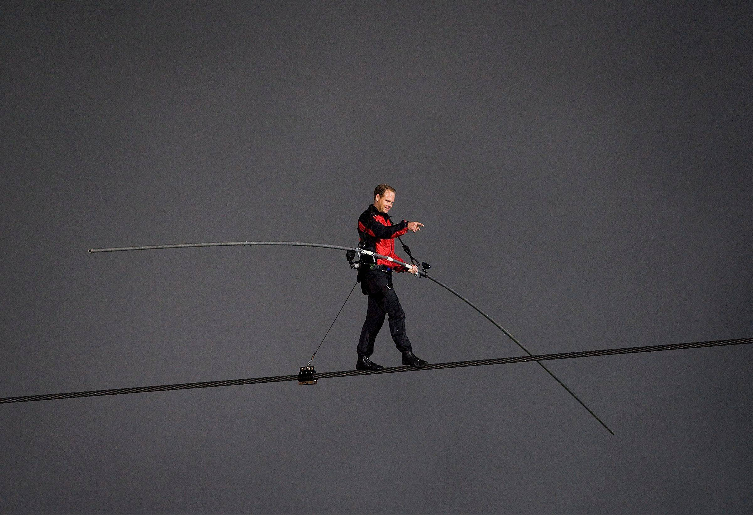 Nik Wallenda points to the crowd of onlookers as he near completion of his 1,800 feet-long tightrope walk over the brink of the Niagara Falls in Niagara Falls, Ont., on Friday, June 15, 2012. Wallenda battled brisk winds and thick mist Friday to make history, becoming the first person to walk across Niagara Falls on a tightrope.