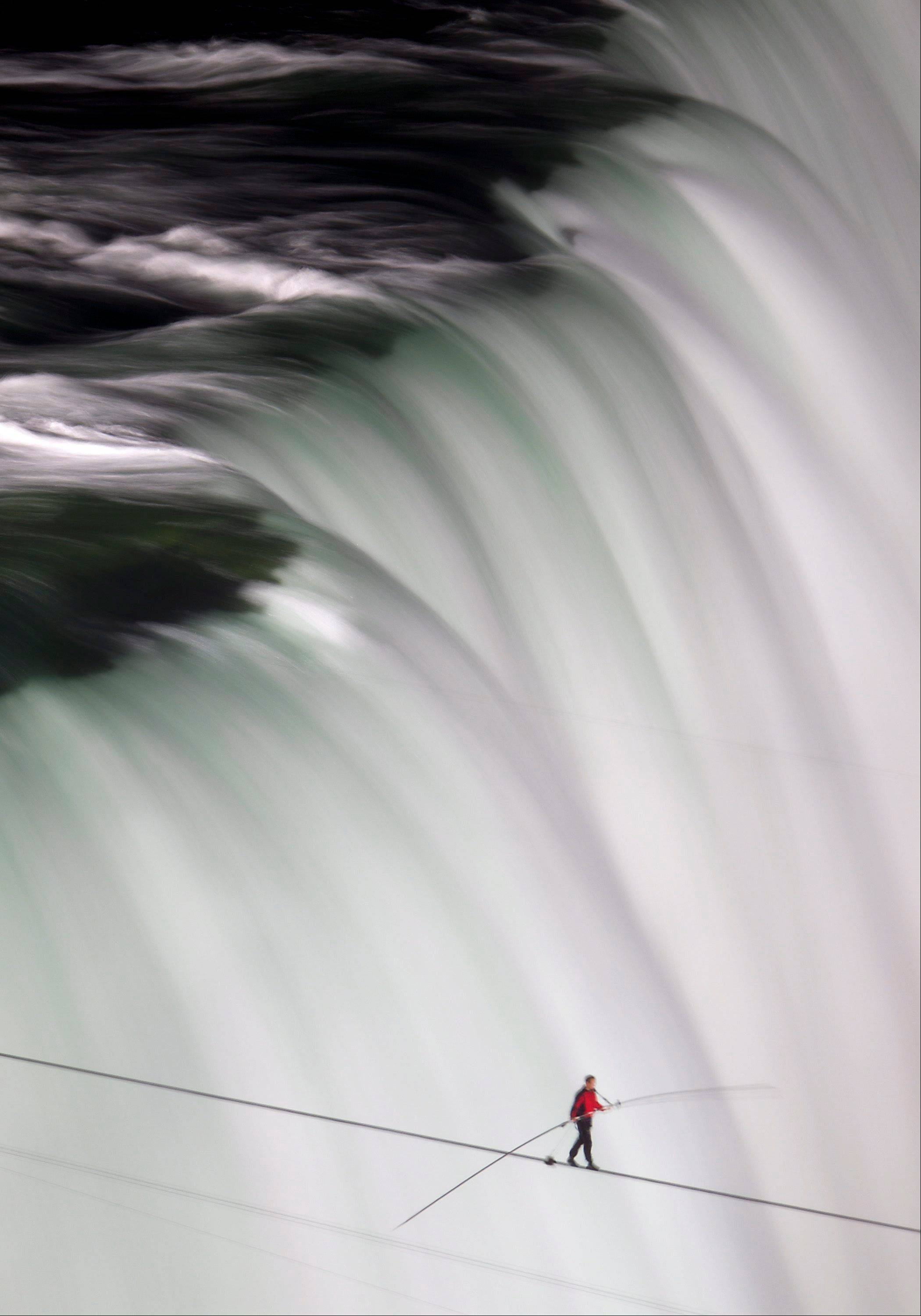 Nik Wallenda walks over Niagara Falls on a tightrope in Niagara Falls, Ontario, on Friday, June 15, 2012. Wallenda has finished his attempt to become the first person to walk on a tightrope 1,800 feet across the mist-fogged brink of roaring Niagara Falls. The seventh-generation member of the famed Flying Wallendas had long dreamed of pulling off the stunt, never before attempted.