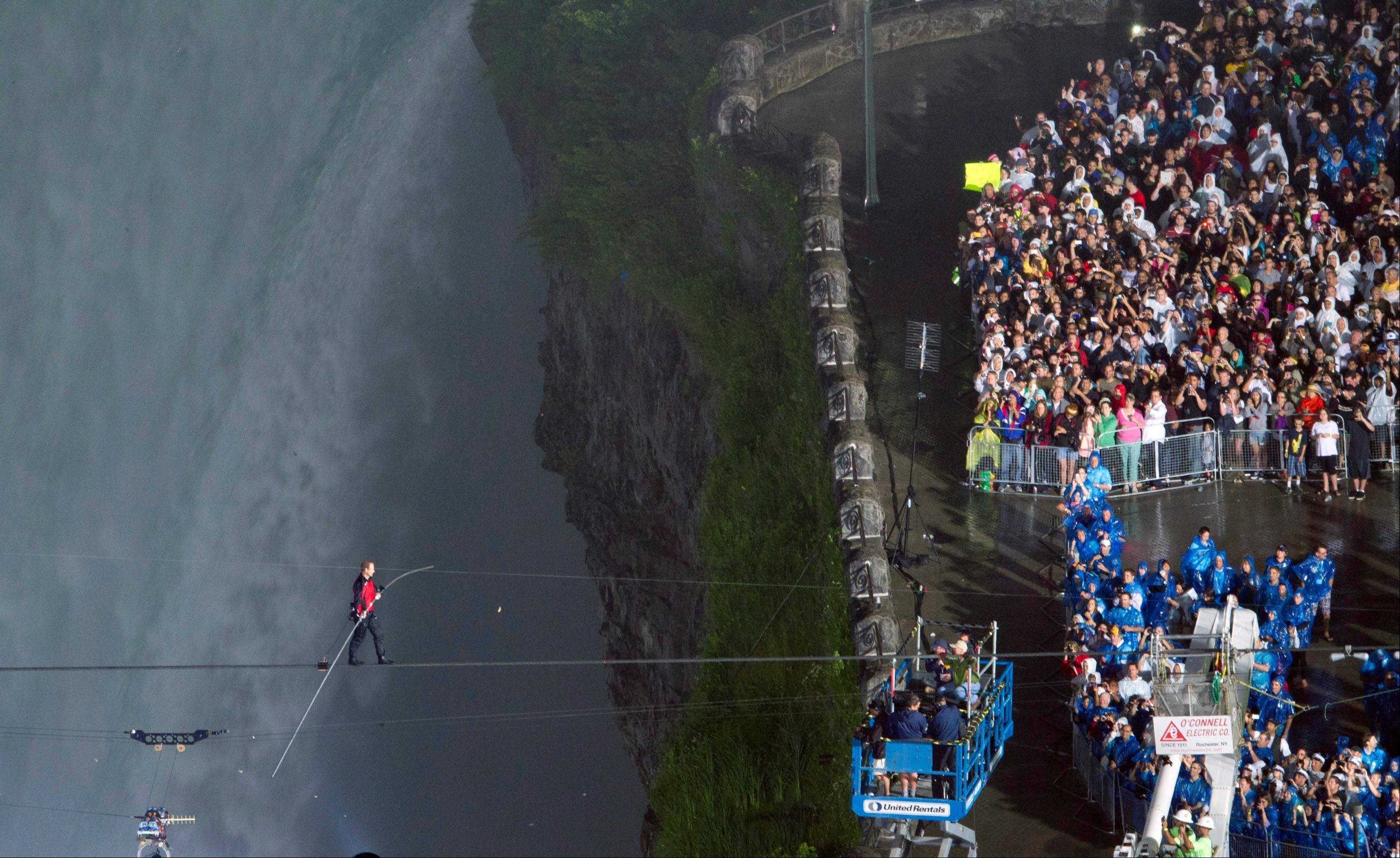 Nik Wallenda completes his walk over Niagara Falls on a tightrope in Niagara Falls, Ont., on Friday, June 15, 2012. Wallenda battled brisk winds and thick mist Friday to make history, becoming the first person to walk across Niagara Falls on a tightrope.