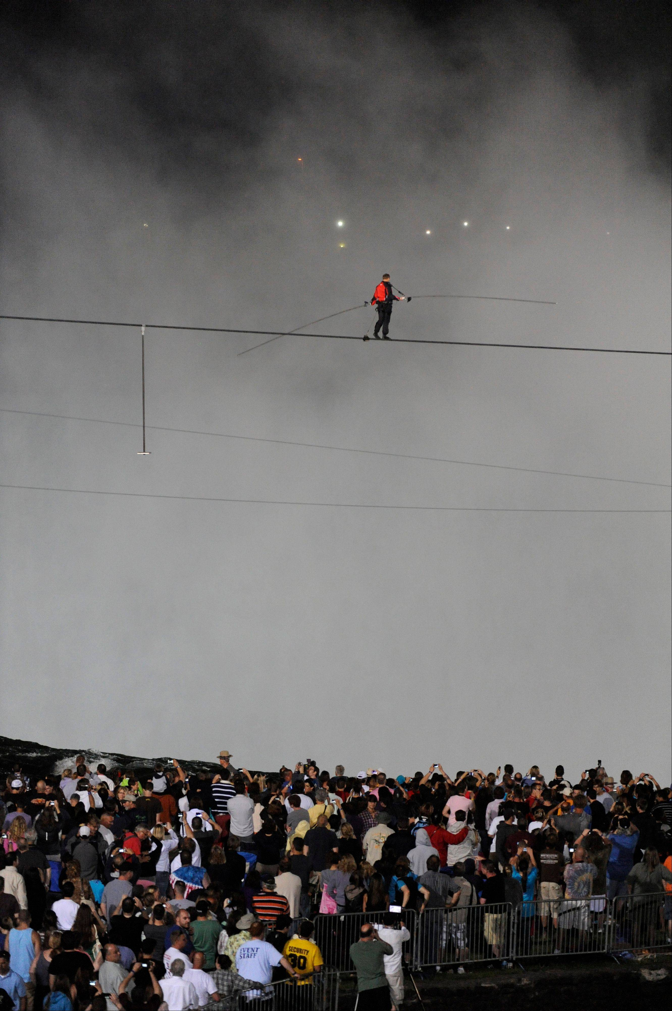 Nik Wallenda walks across Niagara Falls on a tightrope as seen from Niagara Falls, N.Y., Friday, June 15, 2012. Wallenda has finished his attempt to become the first person to walk on a tightrope 1,800 feet across the mist-fogged brink of roaring Niagara Falls. The seventh-generation member of the famed Flying Wallendas had long dreamed of pulling off the stunt, never before attempted.