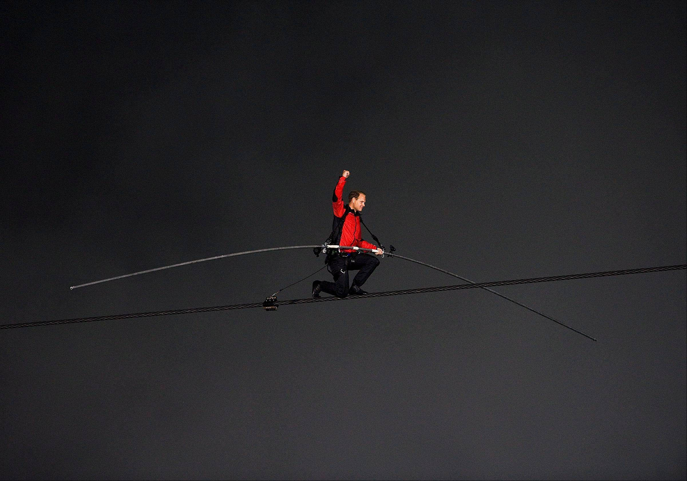 Nik Wallenda pumps his fist on one knee as he nears completion of his 1,800 feet-long tightrope walk over the brink of the Niagara Falls in Niagara Falls, Ont., on Friday, June 15, 2012. Wallenda battled brisk winds and thick mist Friday to make history, becoming the first person to walk across Niagara Falls on a tightrope.
