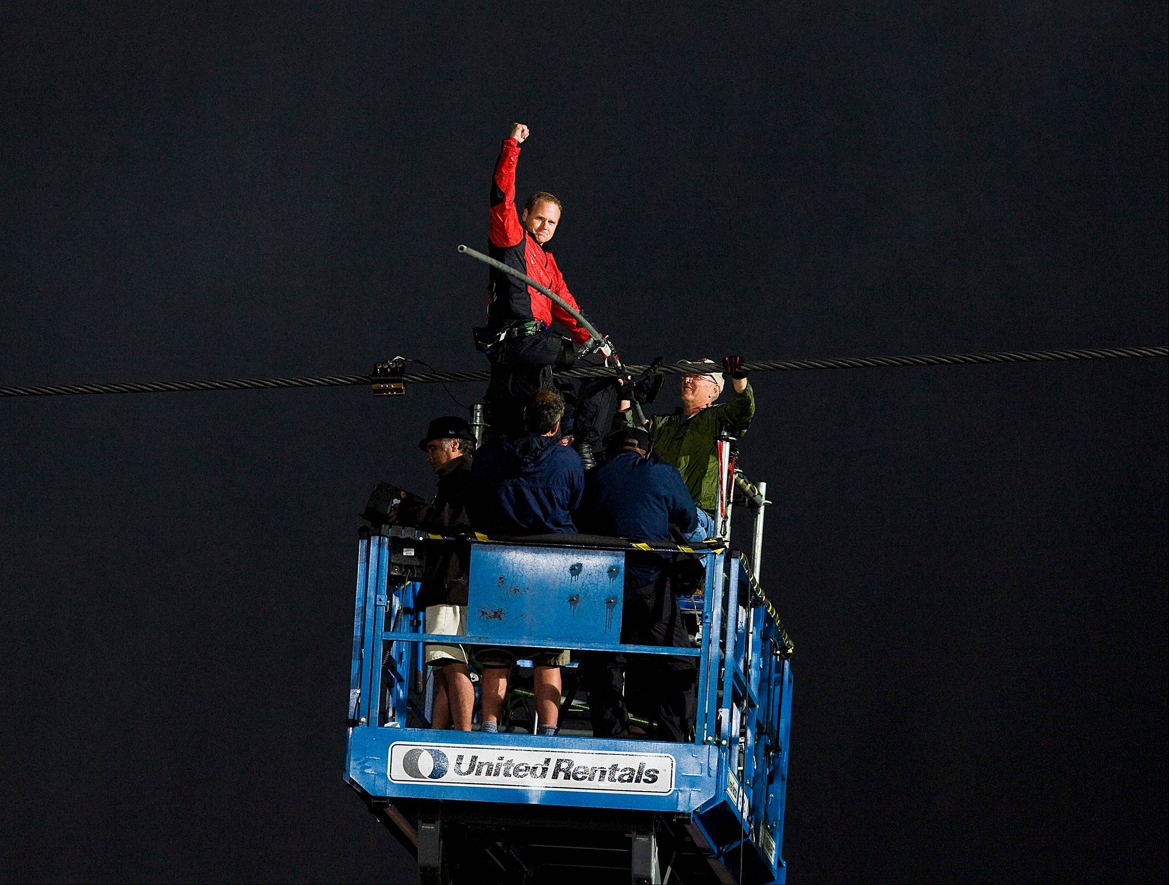 Nik Wallenda pumps his fist as he completes his 1,800 feet-long tightrope walk over the brink of the Niagara Falls in Niagara Falls, Ont., on Friday, June 15, 2012. Wallenda battled brisk winds and thick mist Friday to make history, becoming the first person to walk across Niagara Falls on a tightrope.