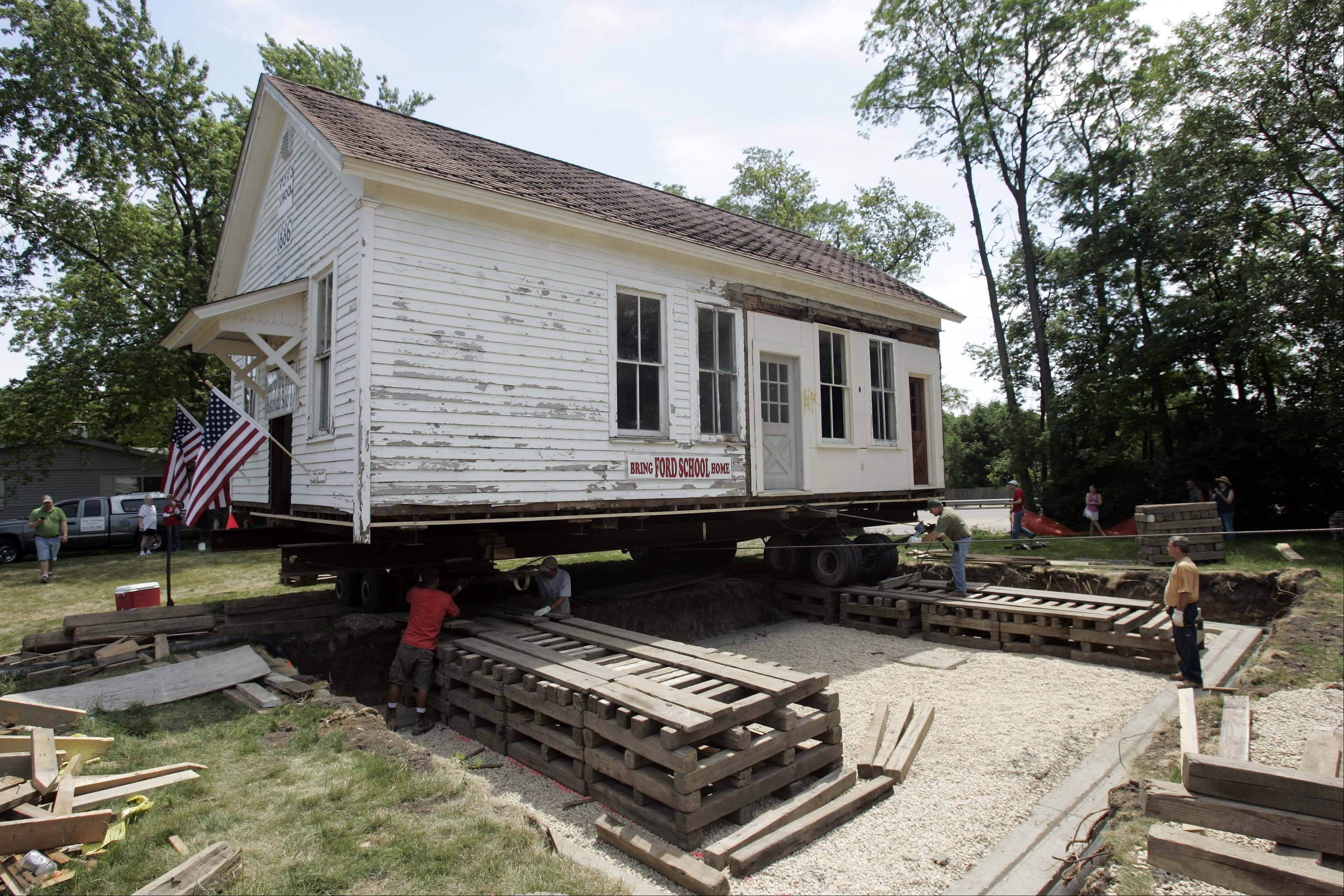 Lyle Hyatt & Co. Inc., of Sandwich, prepares to move the 20-foot by 3-foot, 22-ton Ford schoolhouse into its new location Friday.