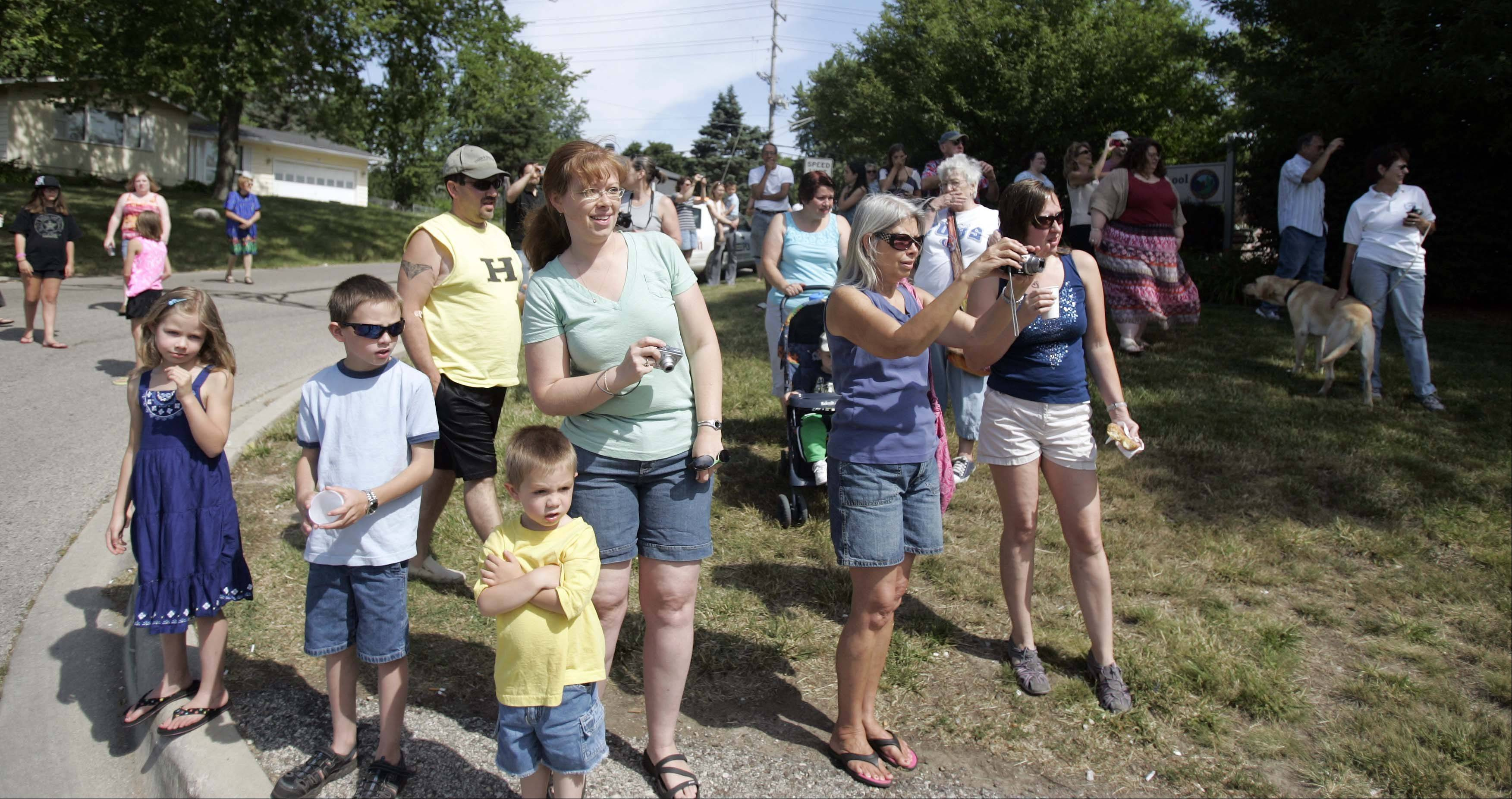 Crowds of people gather Friday to see the Lake in the Hills Historical Society move the Ford schoolhouse back to its original location, four blocks down the road.