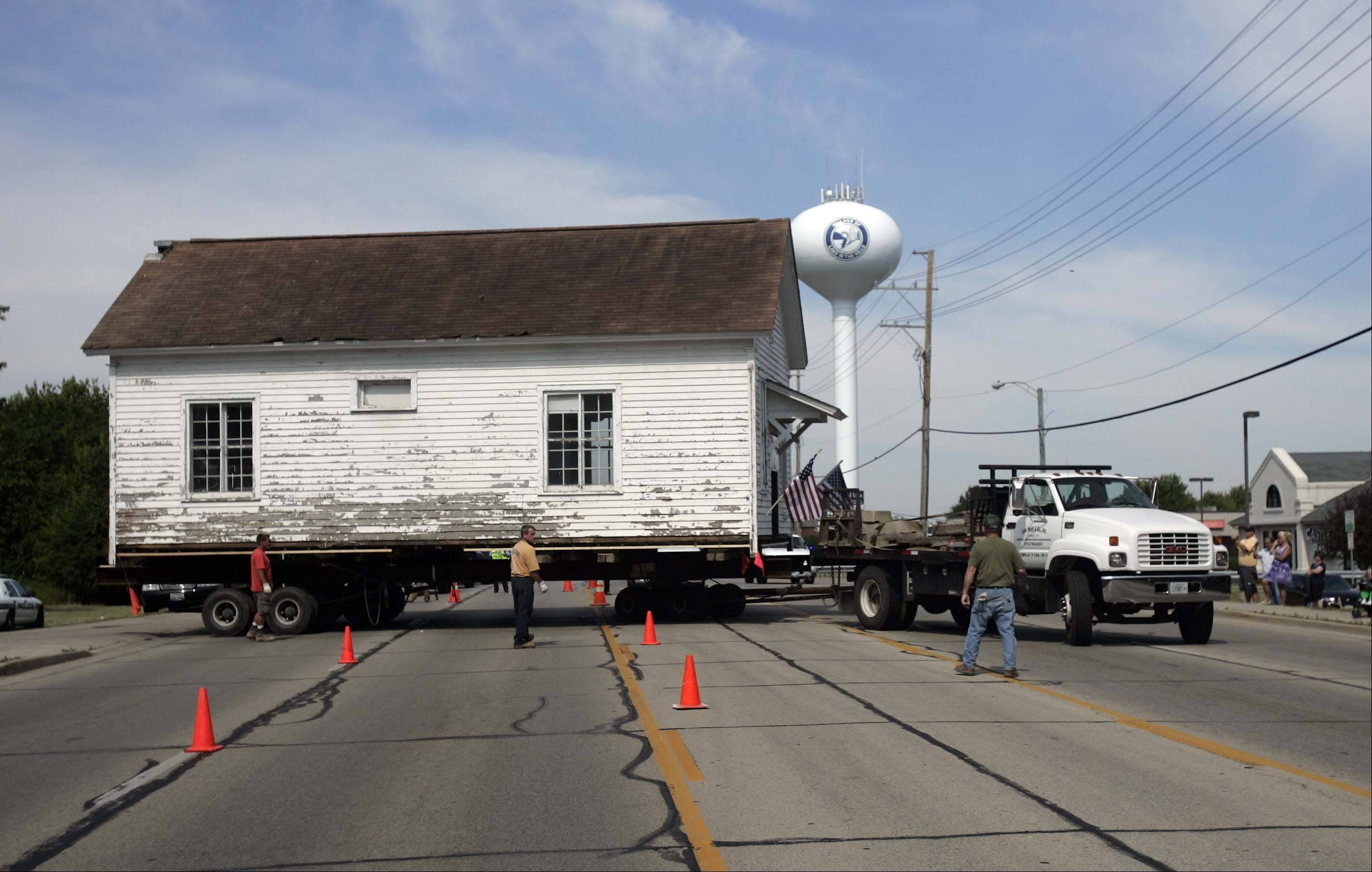 The Ford schoolhouse eases onto Algonquin Road to return to its original location, four blocks down the road.