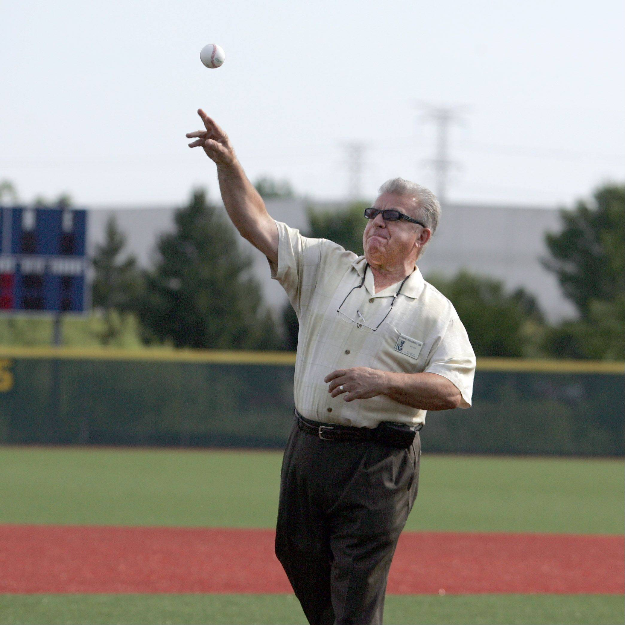 Carol Stream Mayor Frank Saverino throws out one of the first pitches Friday for the opening day of the Legion Post 76 Summer Classic Tournament in Carol Stream. Wheaton Mayor Michael Gresk and Wheaton College Athletic Director Julie Davis also threw out pitches.