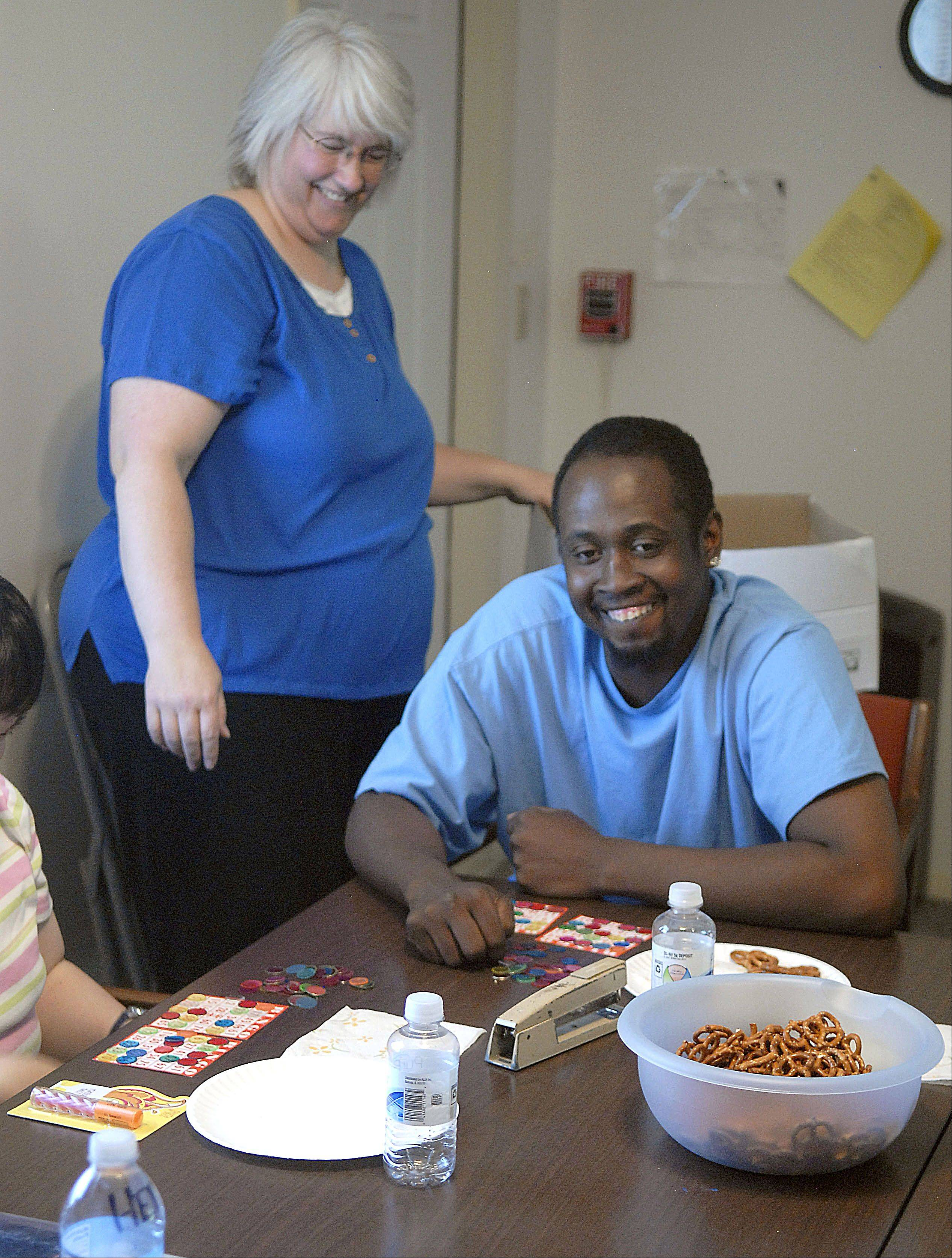Maurice smiles as he and other clients get ready for a game of bingo during a client input meeting at the Association for Individual Development building in Elgin. Lisa Schnell, left, is his direct support person and has been working with him for more than three years.