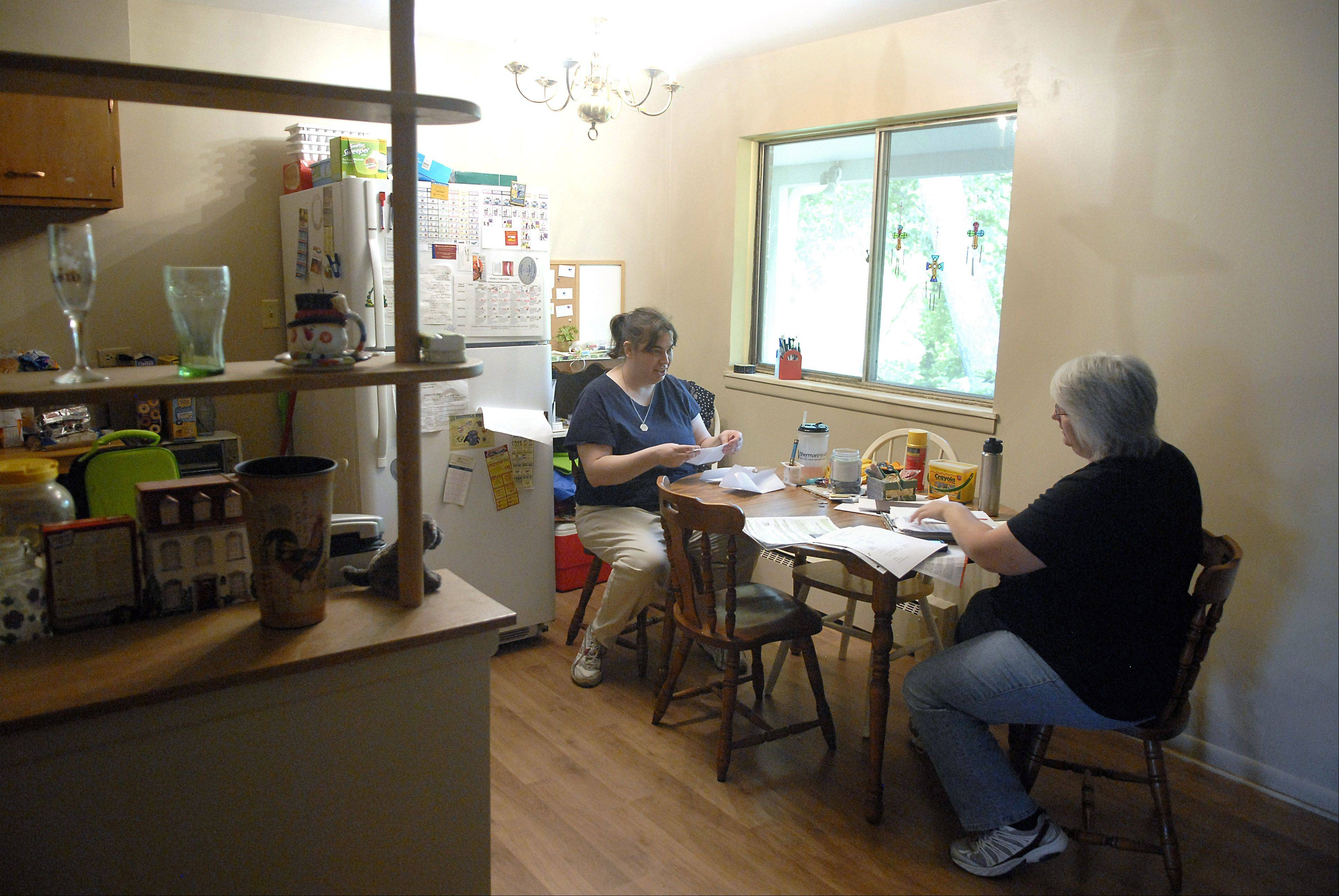 Schnell helps her client Marilyn budget and write out bills on a weekday morning in Marilyn's Elgin condo. Earlier in the morning, Lisa took Marilyn to the doctor for some tests, and would later take her to her job at the East Dundee Wal-Mart.