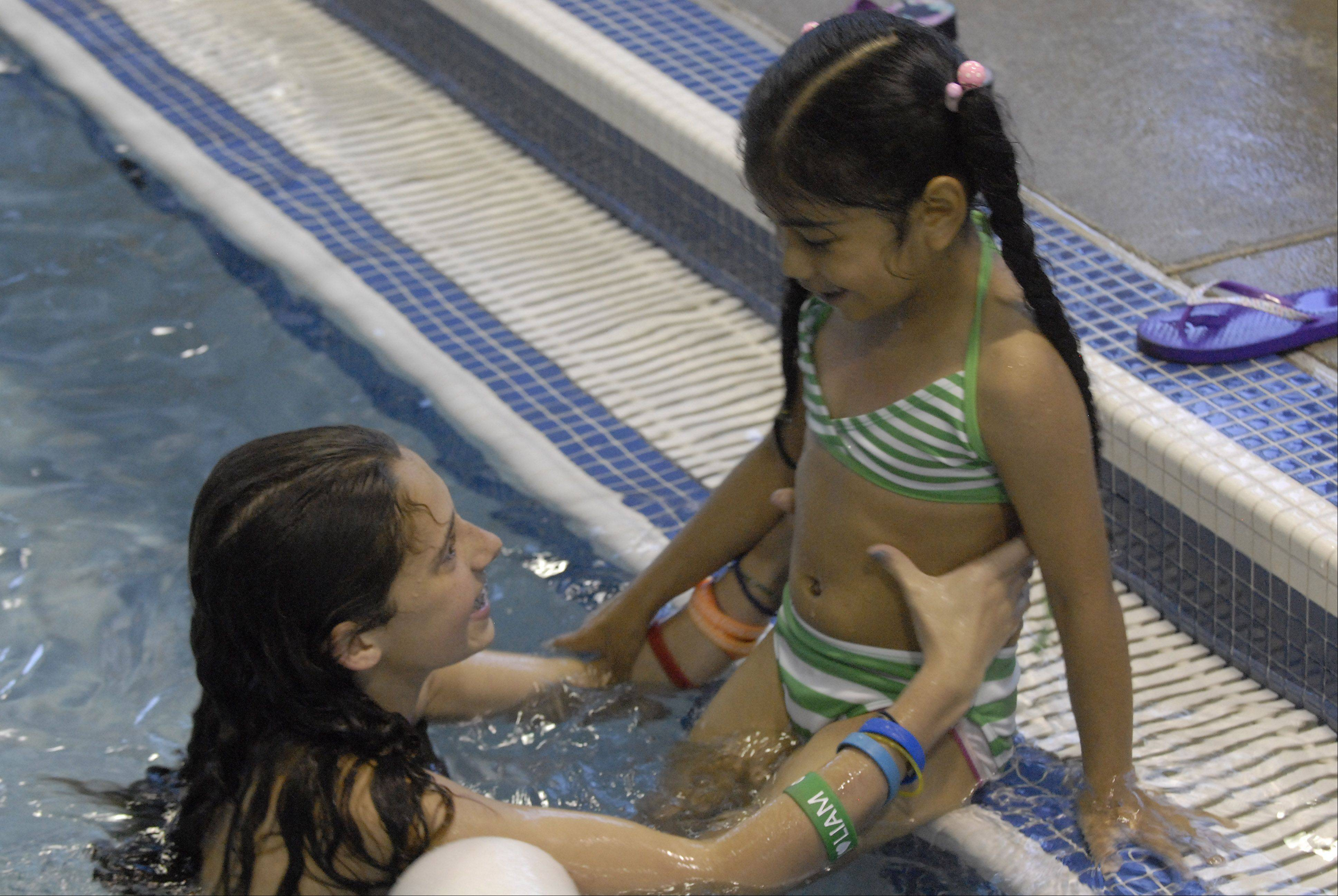 Jenna Cohn, whose brother, Zachary, died in a pool drain accident, helps Perla Maria Saldivar into the Wheeling pool.