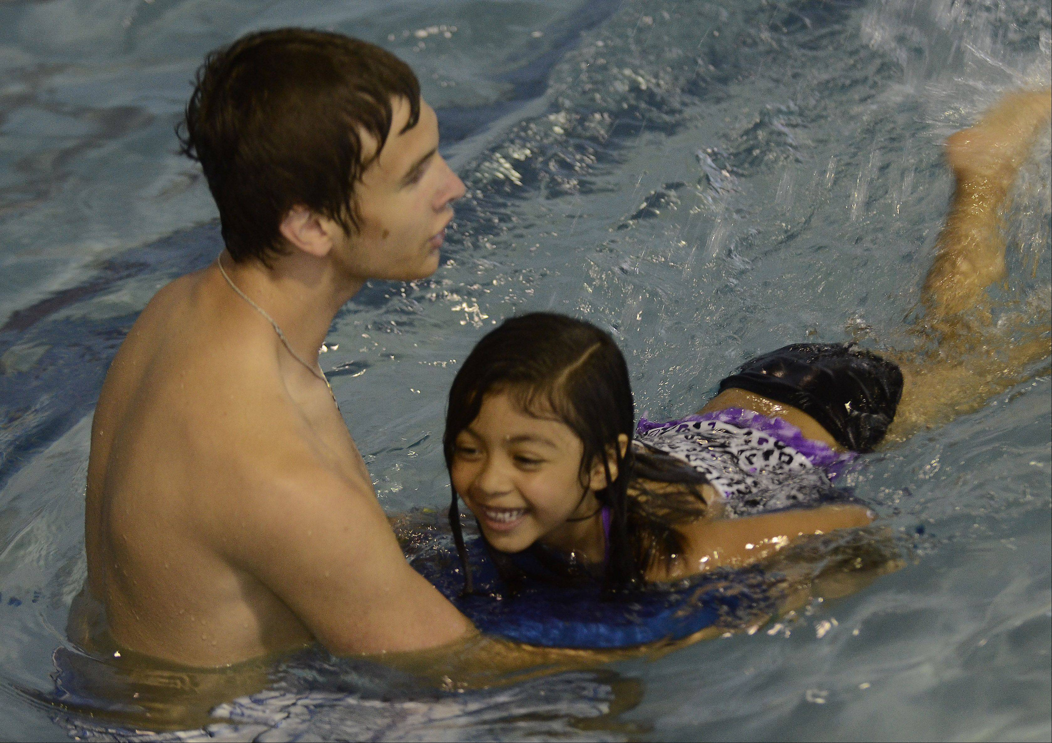 Emily Najera has fun learning to kick, with Blake Gallivan at the first day of water safety camp.