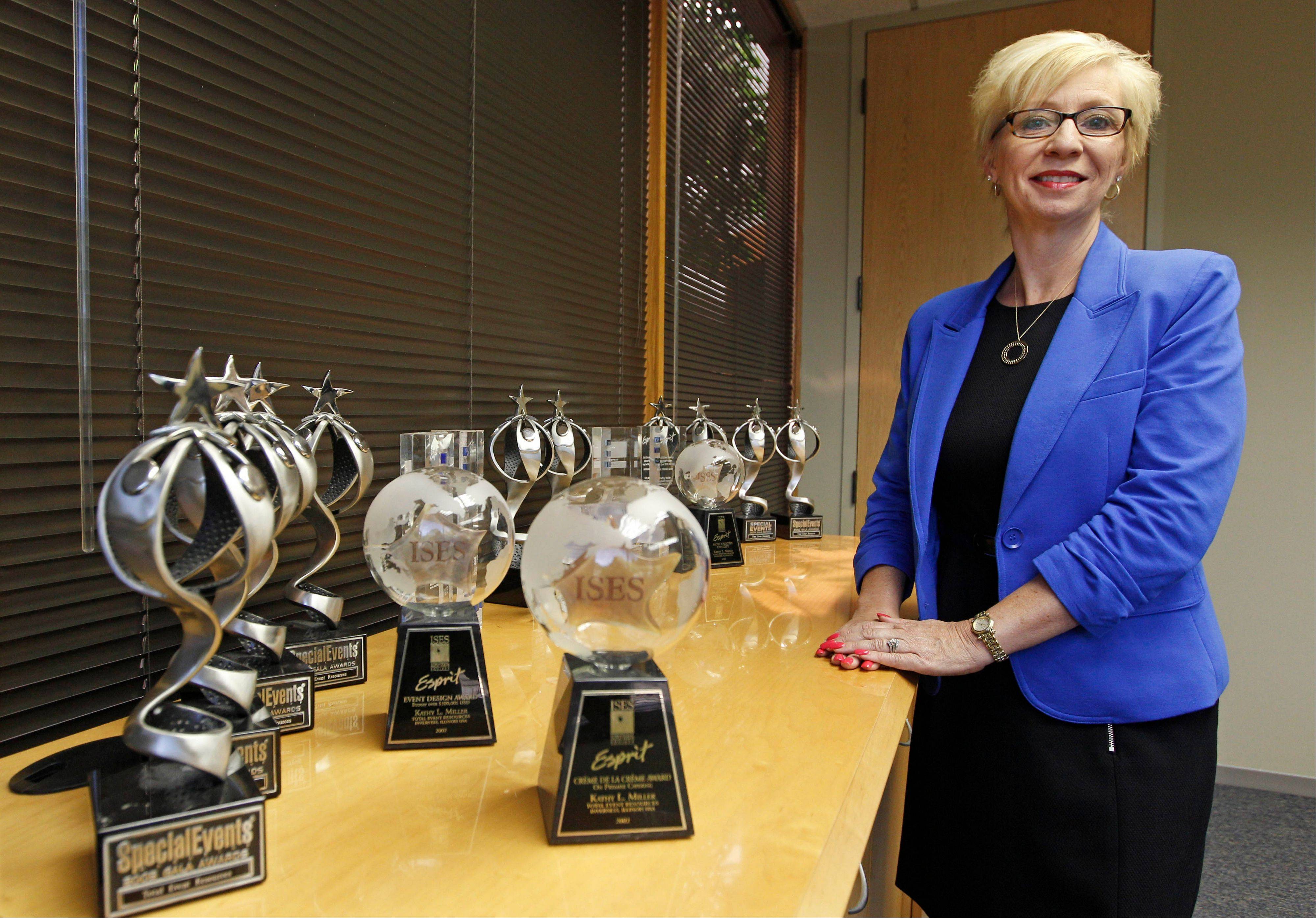 Kathy Miller, president of Total Event Resources, stands next to trophies awarded to her company in her offices in Schaumburg. In 2008, her events planning company was having its best year ever. Then the financial crisis sent the stock market tumbling and the corporate customers who had kept Miller's company busy, stopped calling.
