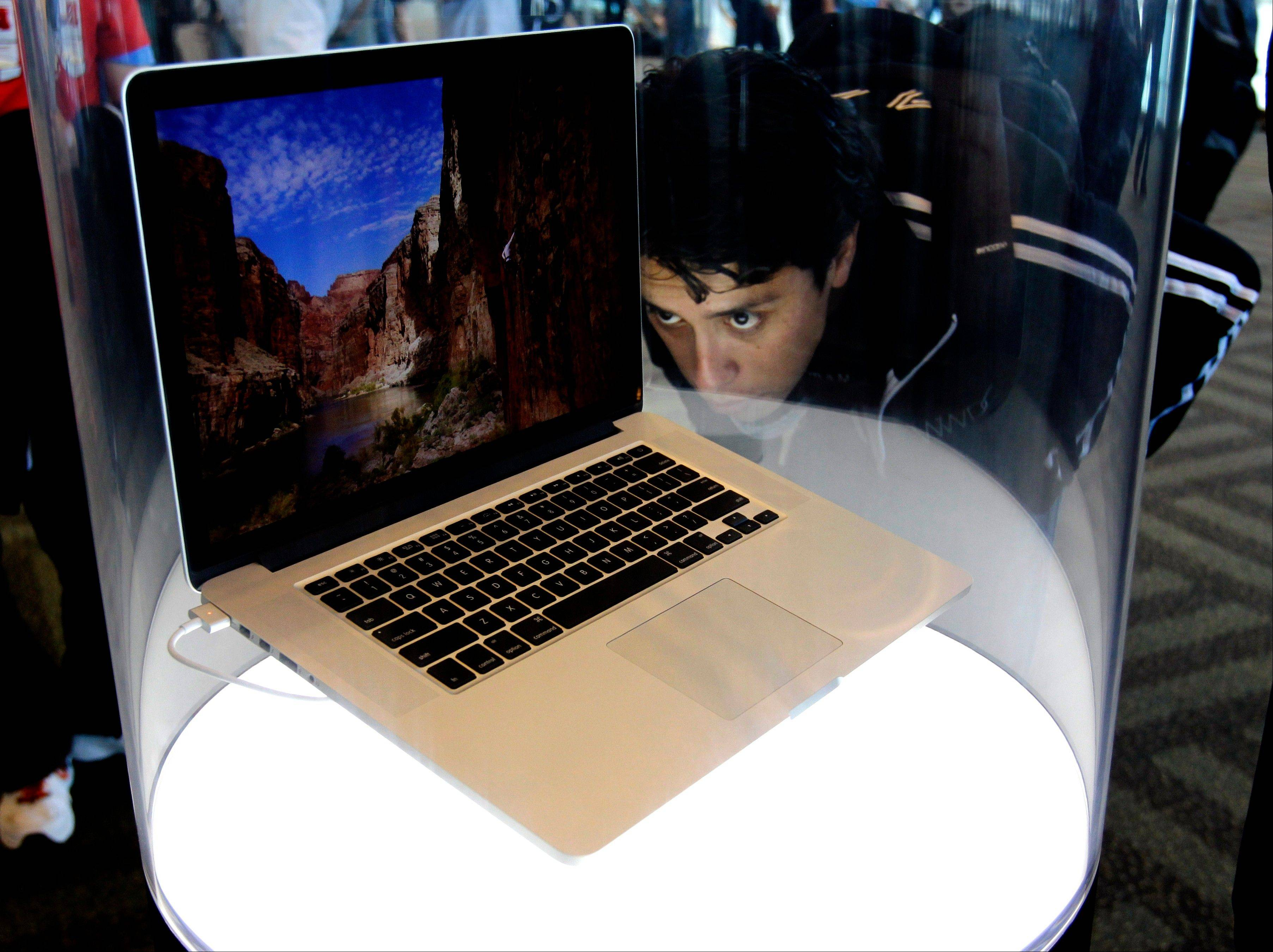 An attendee looks at the new MacBook Pro on display Monday at the Apple Developers Conference in San Francisco. New iPhone and Mac software and updated Mac computers were among the highlights Monday at Apple Inc.'s annual conference for software developers.
