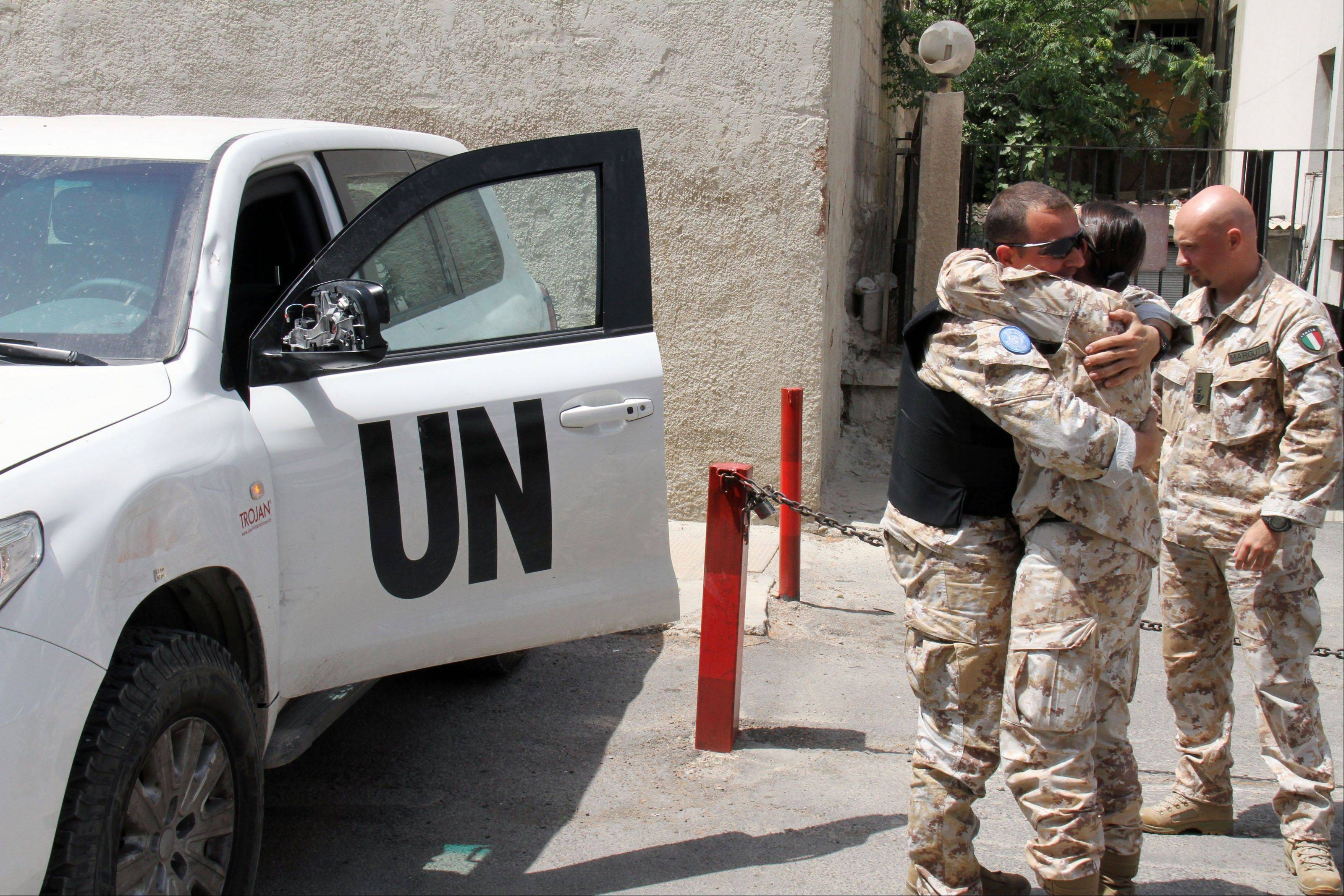 U.N. observers welcome their comrades Saturday upon their return from al-Haffa, in northern Syria, to Damascus.