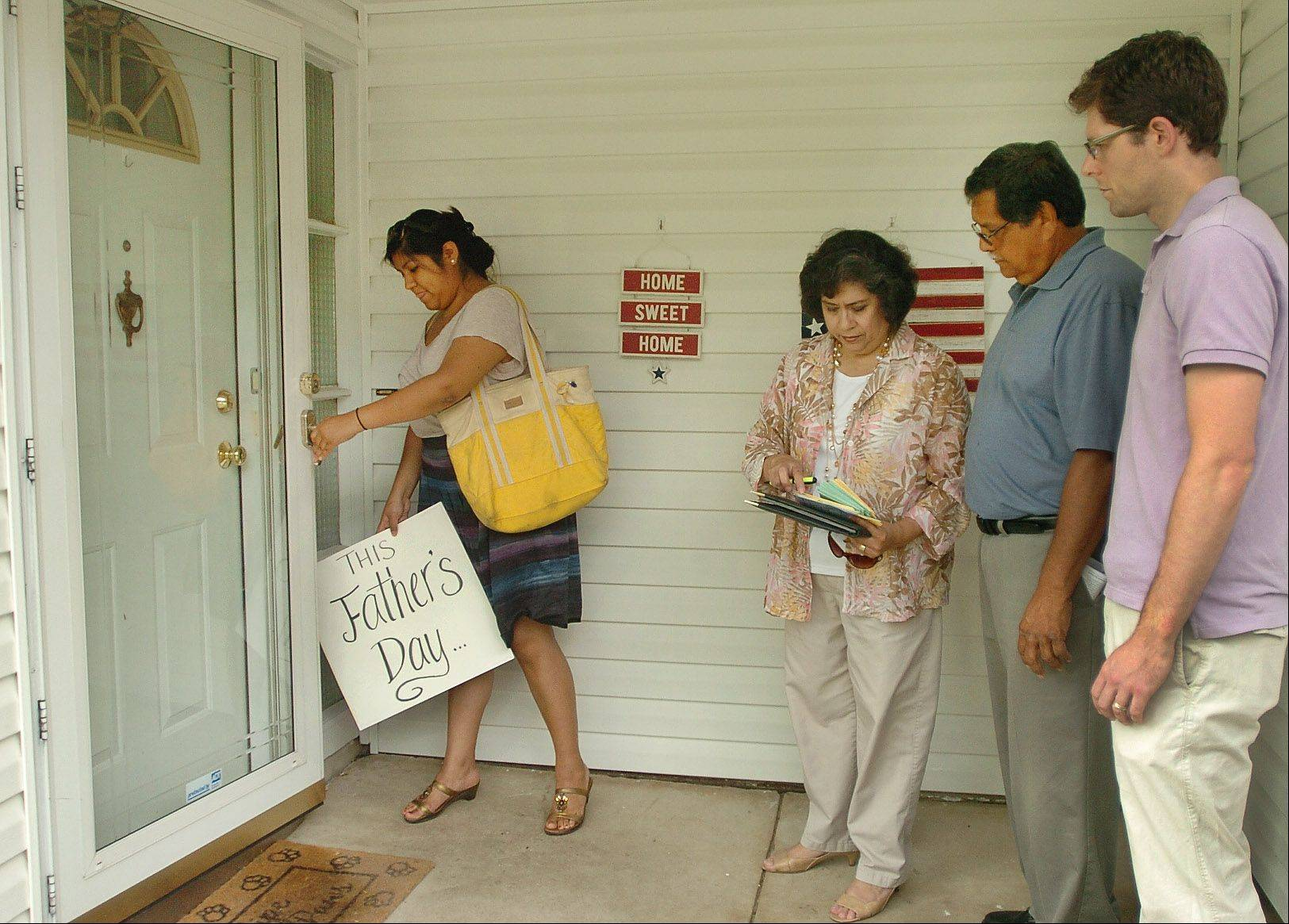 Maria Salazar places a sign in the doorway of state Rep. Fred Crespo's home as members of the Illinois Coalition for Immigrant and Refugee Rights deliver Father's Day cards and letters to Crespo's home Saturday in protest of his policies on immigration.