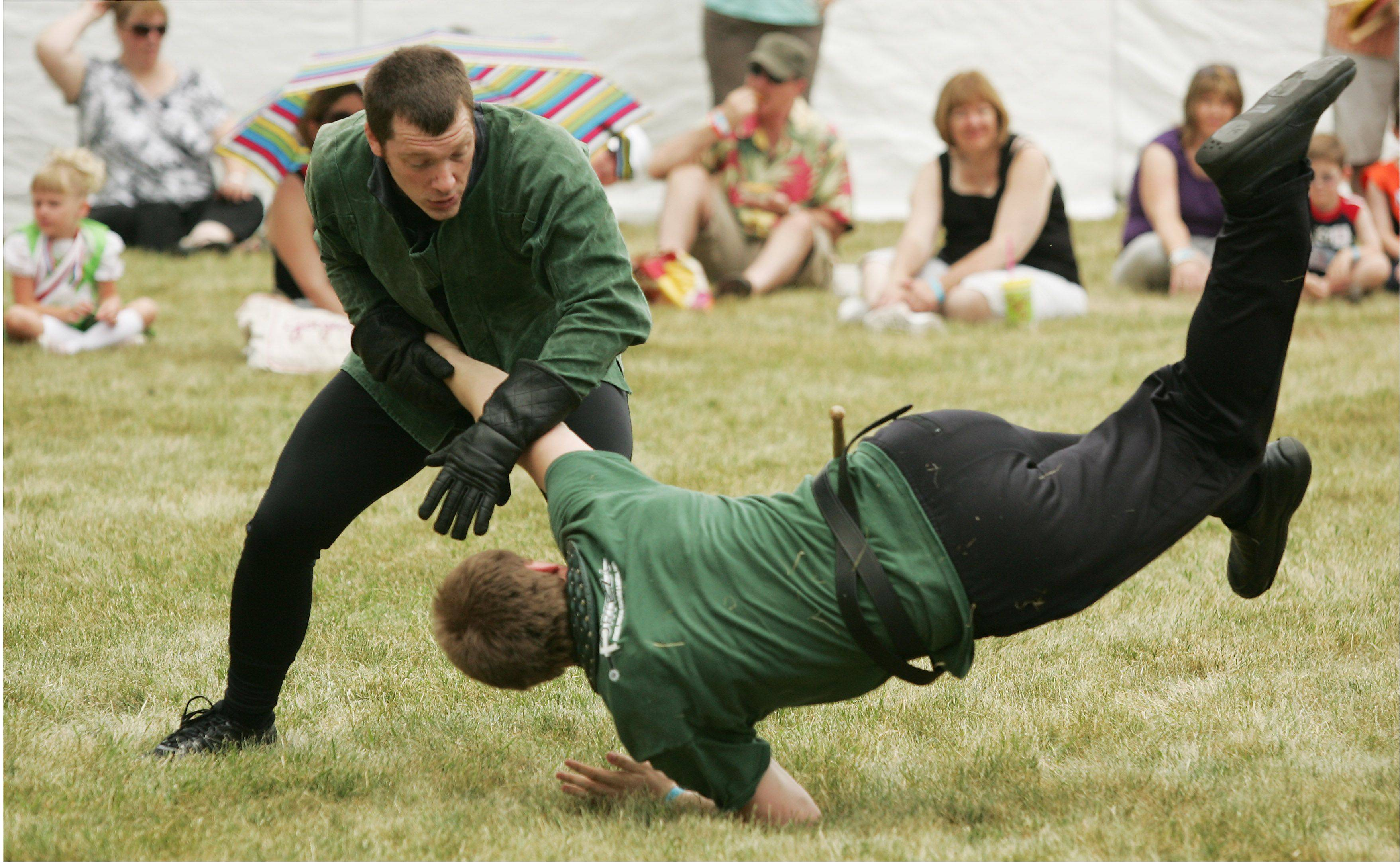 Jesse Kulla of Chicago and Nathan Wisniewski of Arlington Heights, members of the Chicago Swordplay Guild, demonstrate grappling techniques Saturday during the Illinois St. Andrew Society Scottish Festival and Highland Games at Hamilton Lakes in Itasca.
