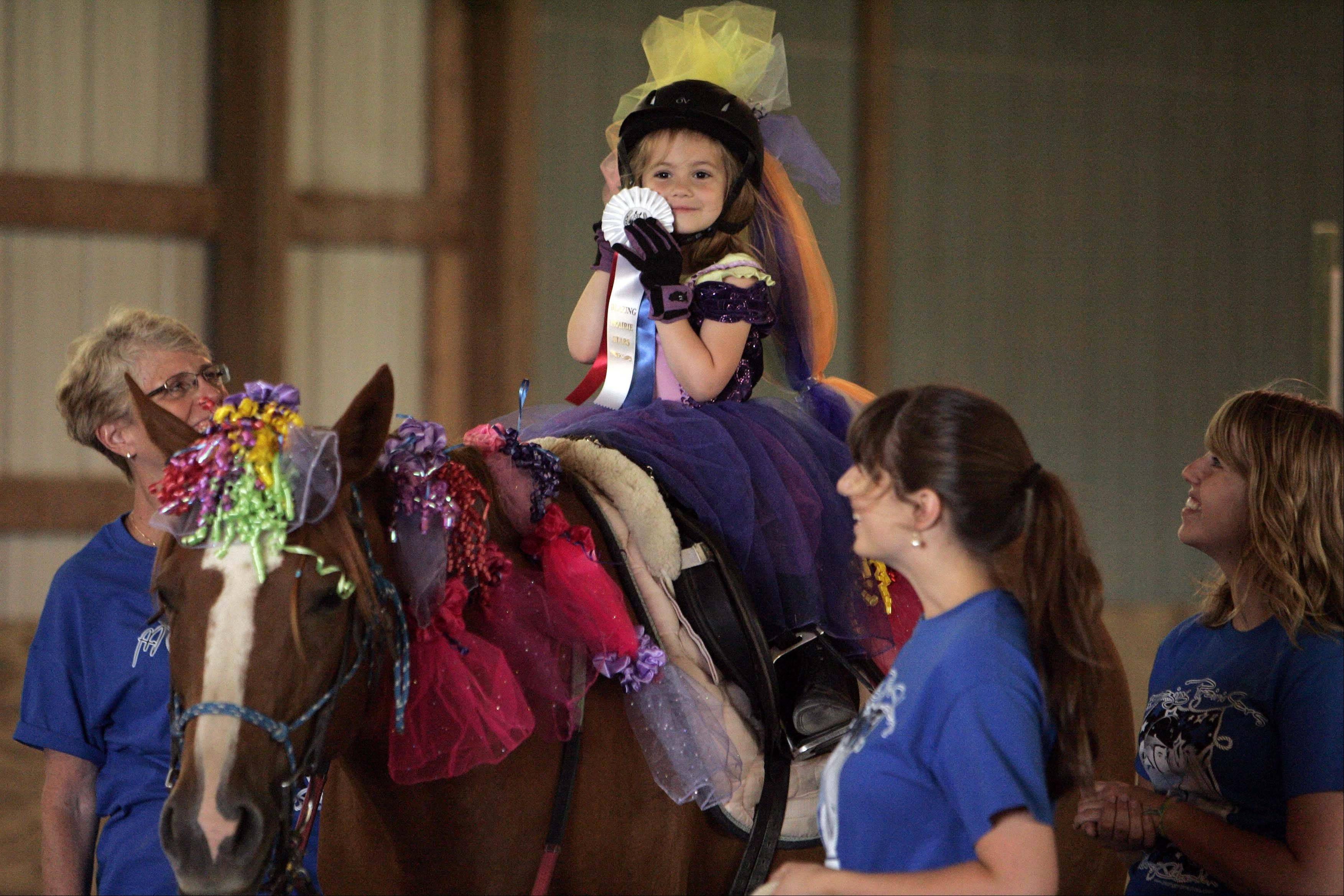 Dressed as a princess, Madelyn Kennedy, 4, of Batavia, shows off her ribbon for competing in the 2012 Star Riders Celebration. The facility, built in 2001, provides therapeutic riding and hippotherapy sessions to children with special needs.