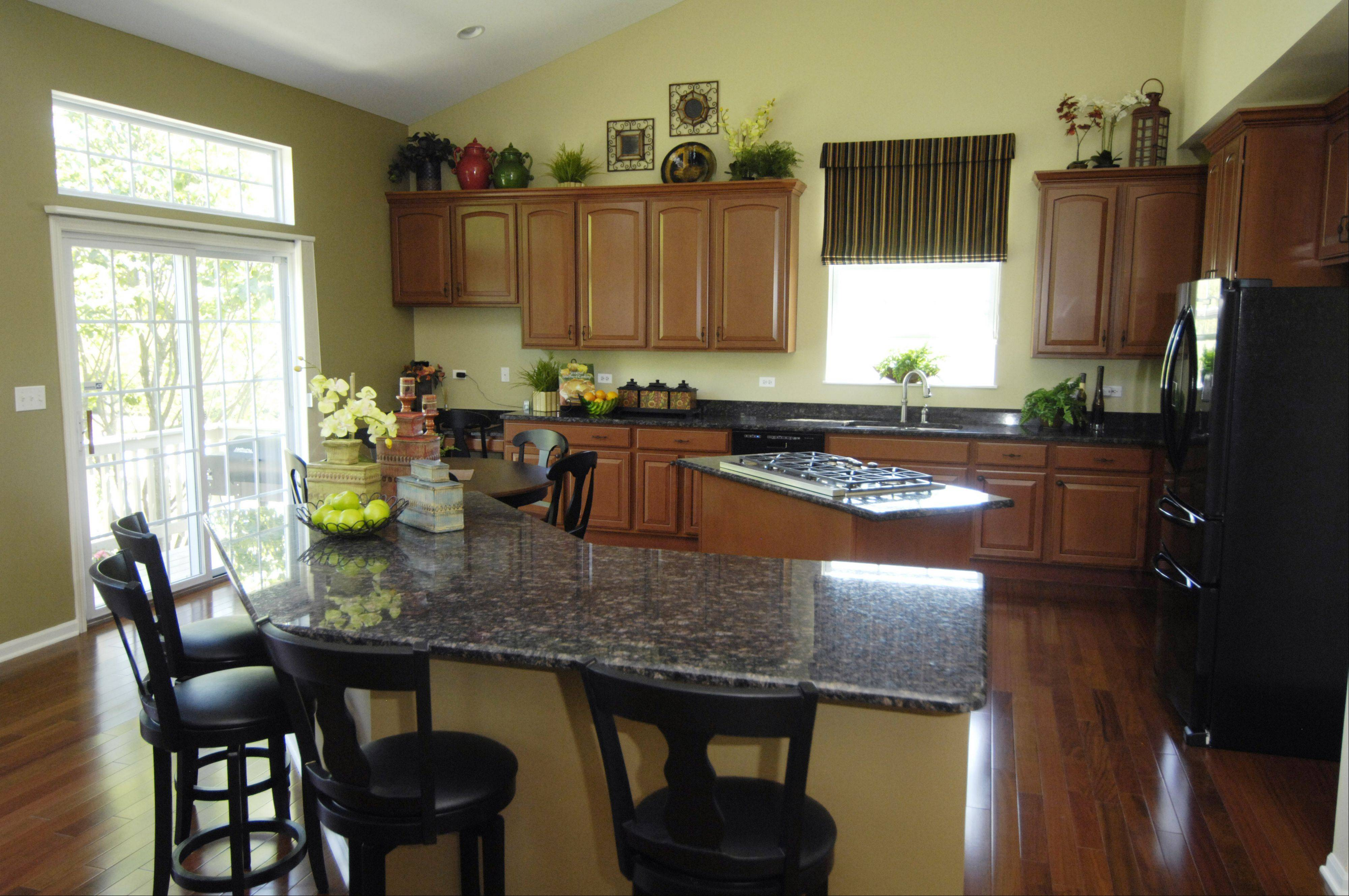 The granite, flooring and furniture is new, but the cabinets were refinished from a light pickled effect with pink tones.