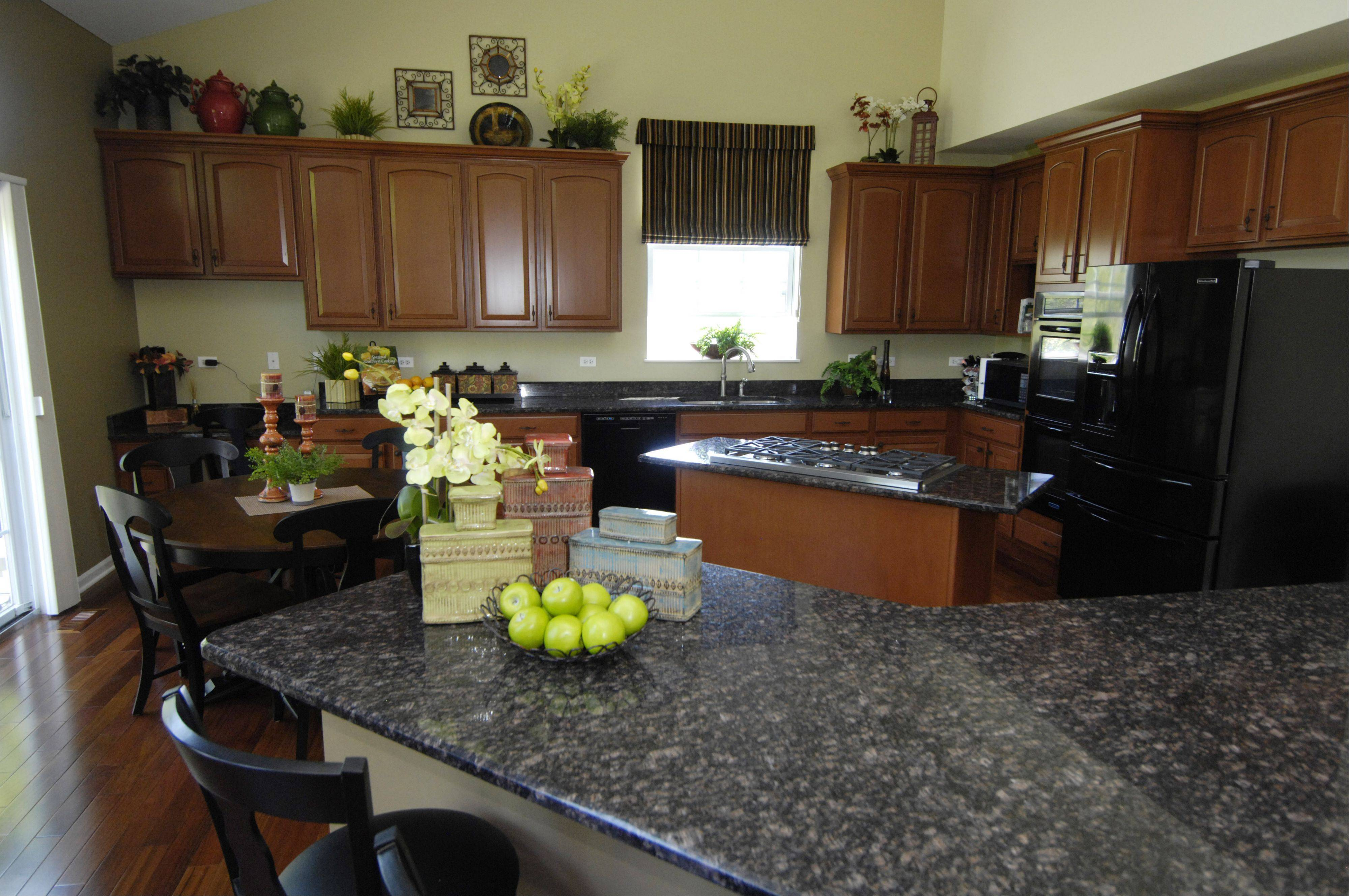 The layout of the kitchen remained the same but a new look comes from refinished cabinets, a new wall color, a black granite countertop and cherry wood flooring.