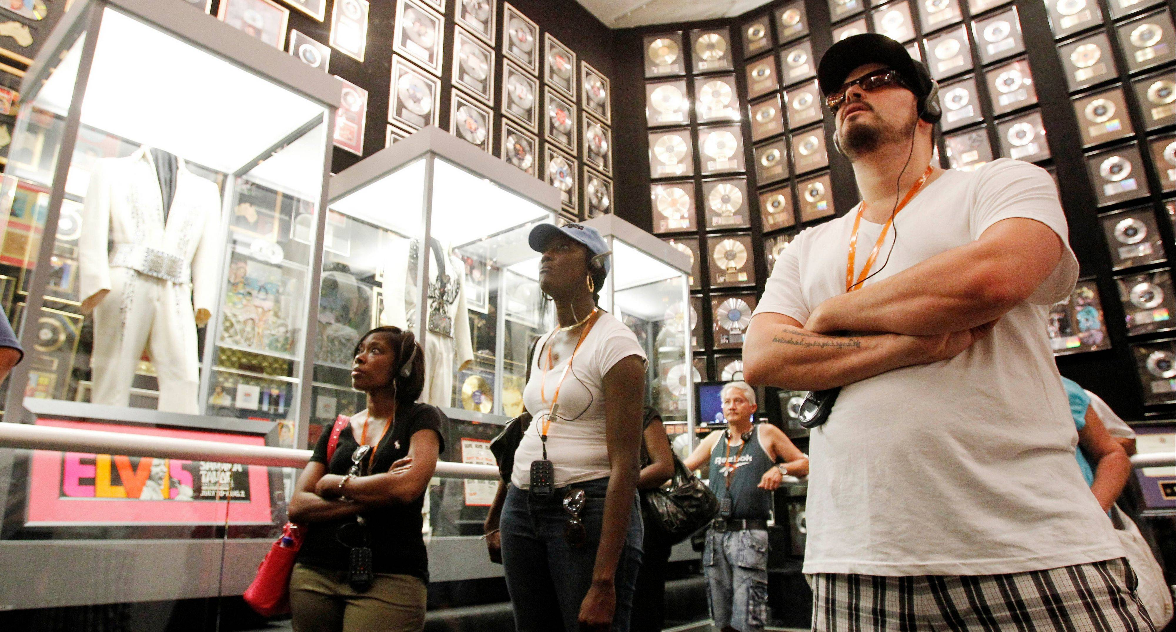 Tourists explore the trophy room at Graceland.