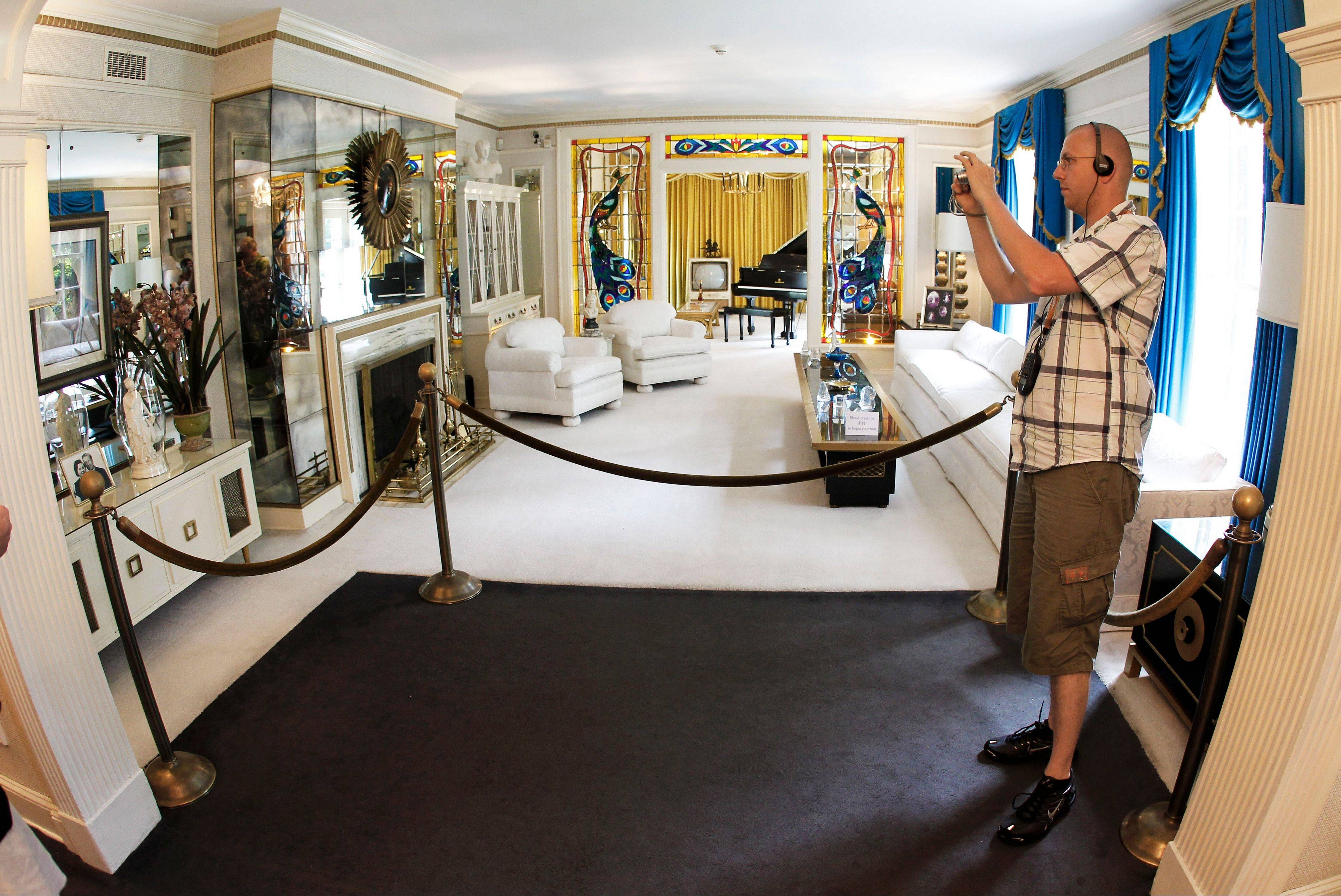 A tourist views the living room at Graceland.