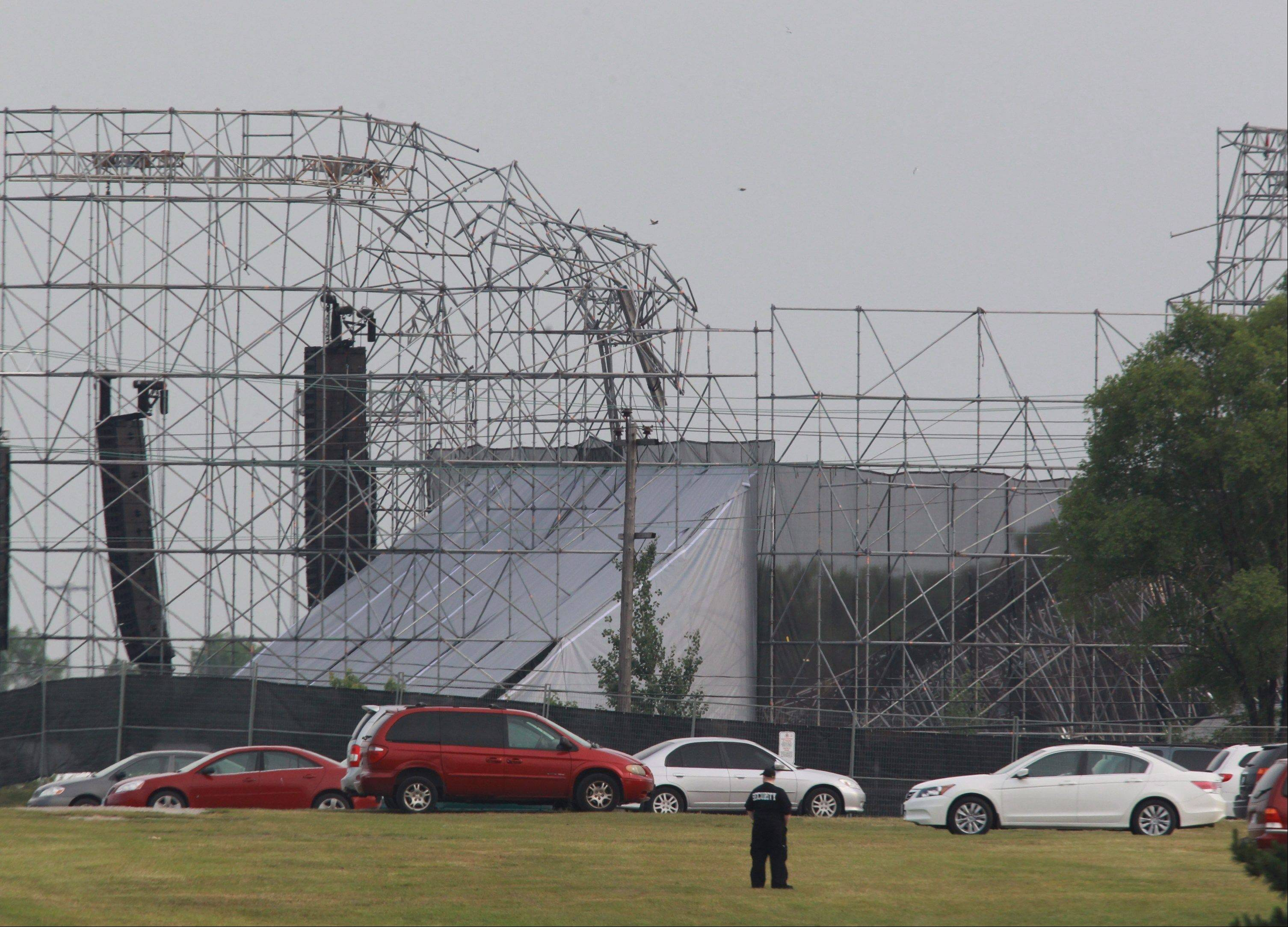 A security guard surveys the scene near a collapsed concert stage at Downsview Park in Toronto, Saturday, June 16, 2012. The top of a stage being set up for a concert by the alternative rock band Radiohead collapsed, killing one of the stage workers preparing for the event.