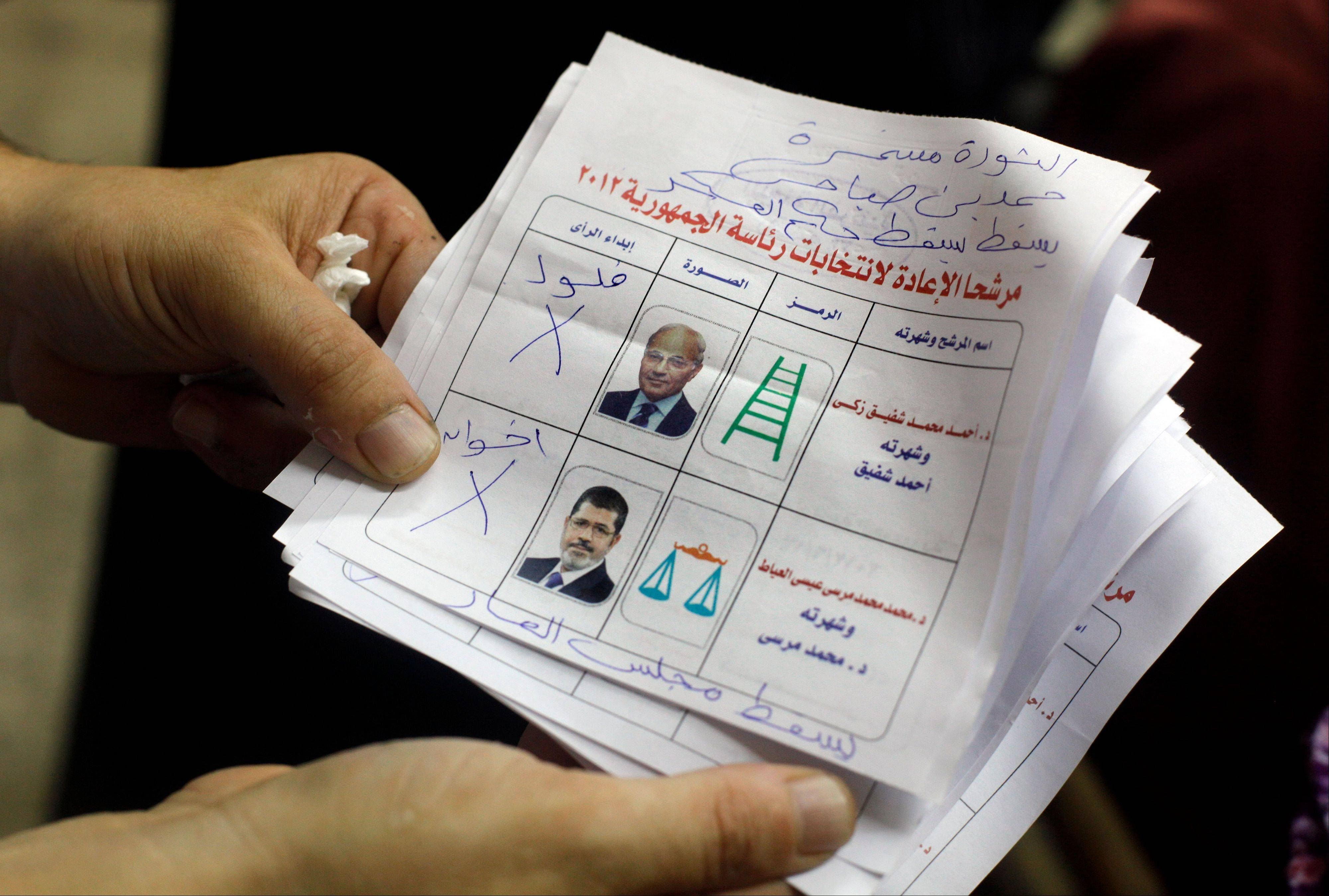 An Egyptian elections official holds unusable ballots at a polling center after the second day of the presidential runoff, in Cairo, Egypt, Sunday.