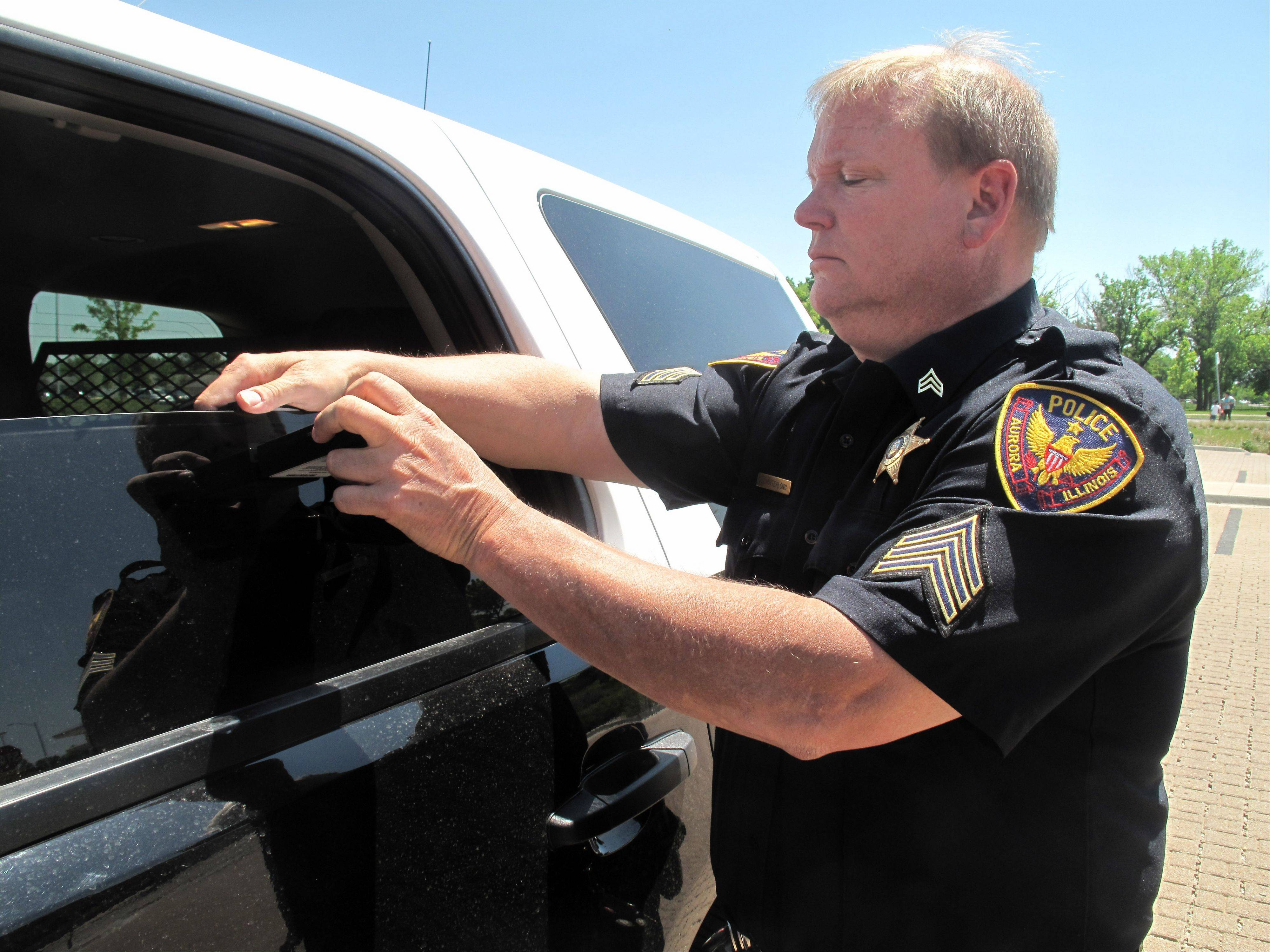 Sgt. Tom Hinterlong uses a light transmittance meter to determine how much light can shine through the front driver's side window of his squad car. Aurora police got their first light meter in April and have been using it to test the tint of car windows stopped during traffic details.