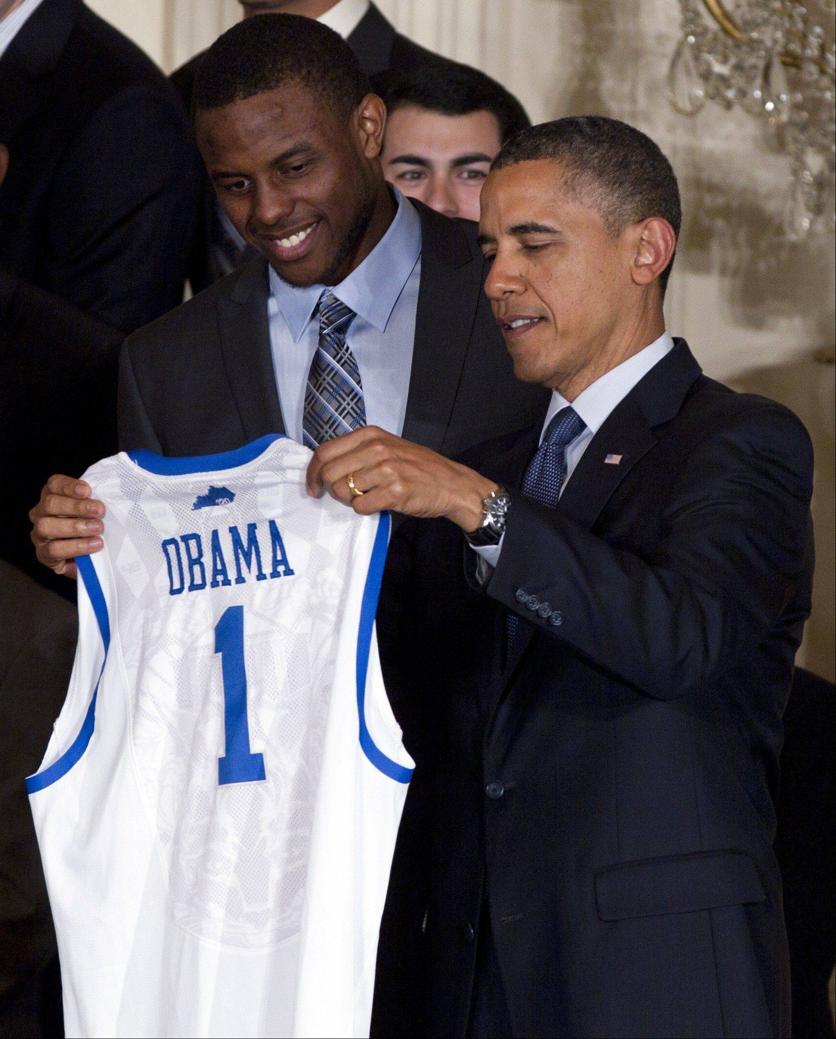 President Barack Obama accepts a University of Kentucky basketball jersey from guard Darius Miller during a celebration for the NCAA men's championship team May 4 at the White House.