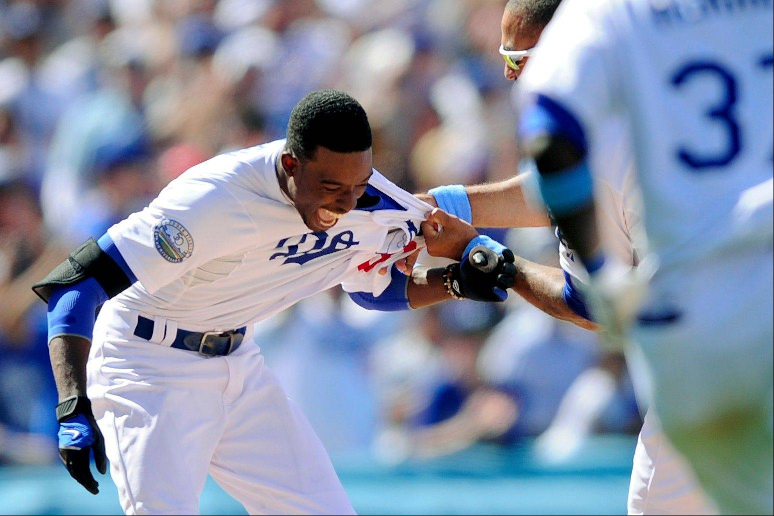 The Los Angeles Dodgers' Dee Gordon celebrates with teammates Sunday after he driving in the winning run in the 10th inning against the White Sox.