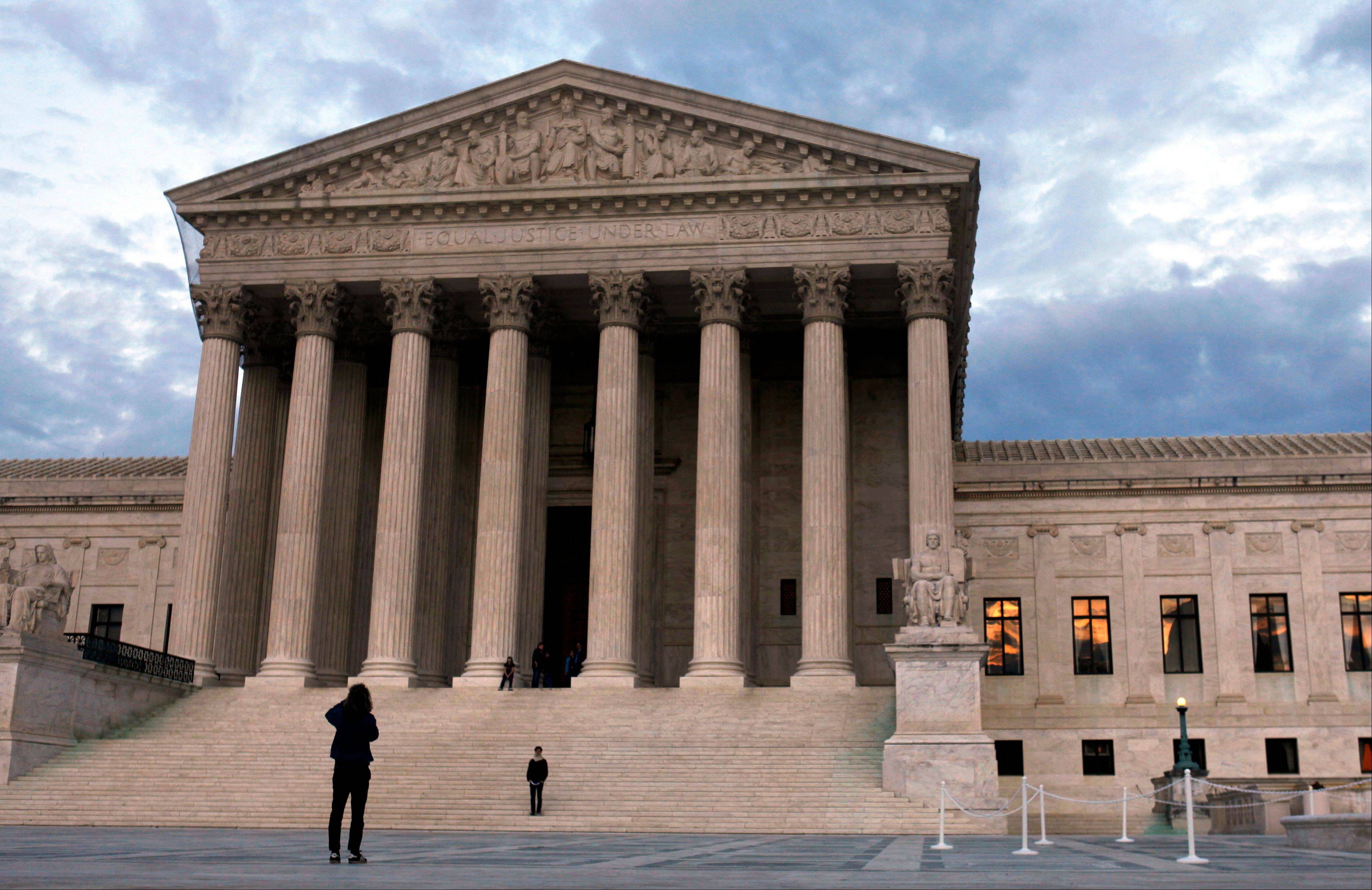 People visit the Supreme Court in Washington last March. Three top insurers say they'll honor some provisions of the U.S. Affordable Care Act, even if the Supreme Court overturns the health care law.