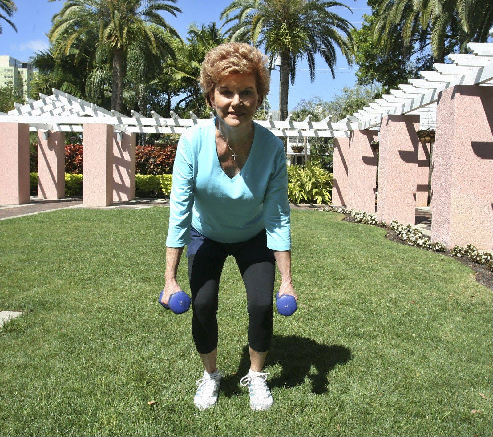 Starin Shouppe demonstrates how to do squats with weights, a lower-body exercise.