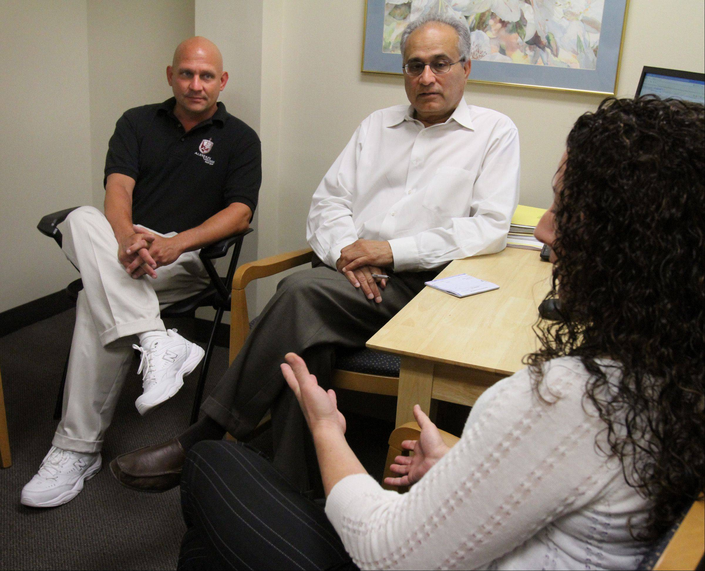 Dr. Deepak Kapoor, medical director for the Partial Hospitalization Program, center, talks with Katie Connolly, PHP team leader, right, and Rick Germann, director of operations at the Alexian Brothers Center for Mental Health in Arlington Heights on Wednesday.
