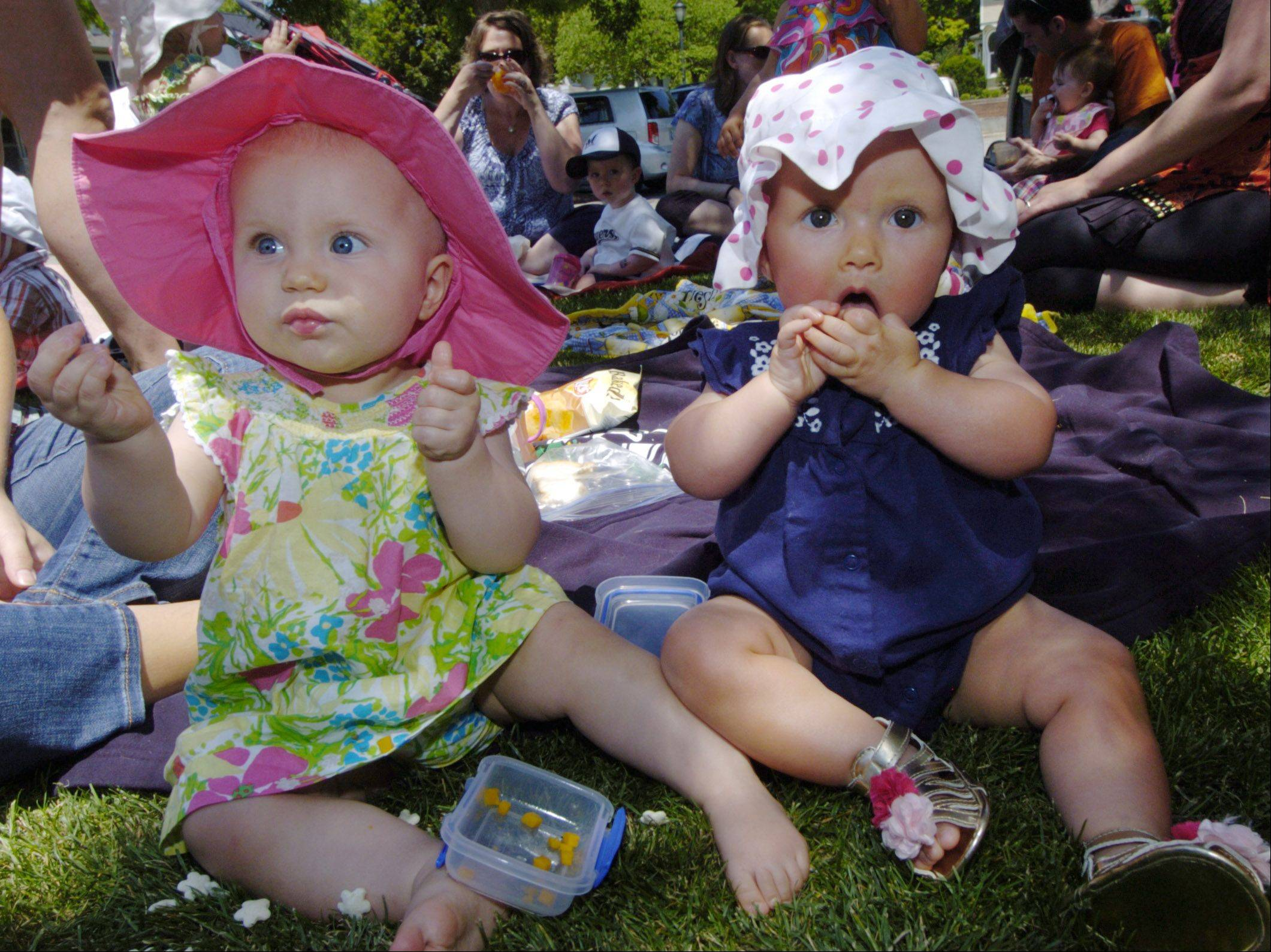 Katherine Edwards, age 10 months, left, of Arlington Heights and Gianna Suvada, also 10 months, of Schaumburg have lunch together as the Arlington Park District kicks off summer with a picnic at North School Park Friday.