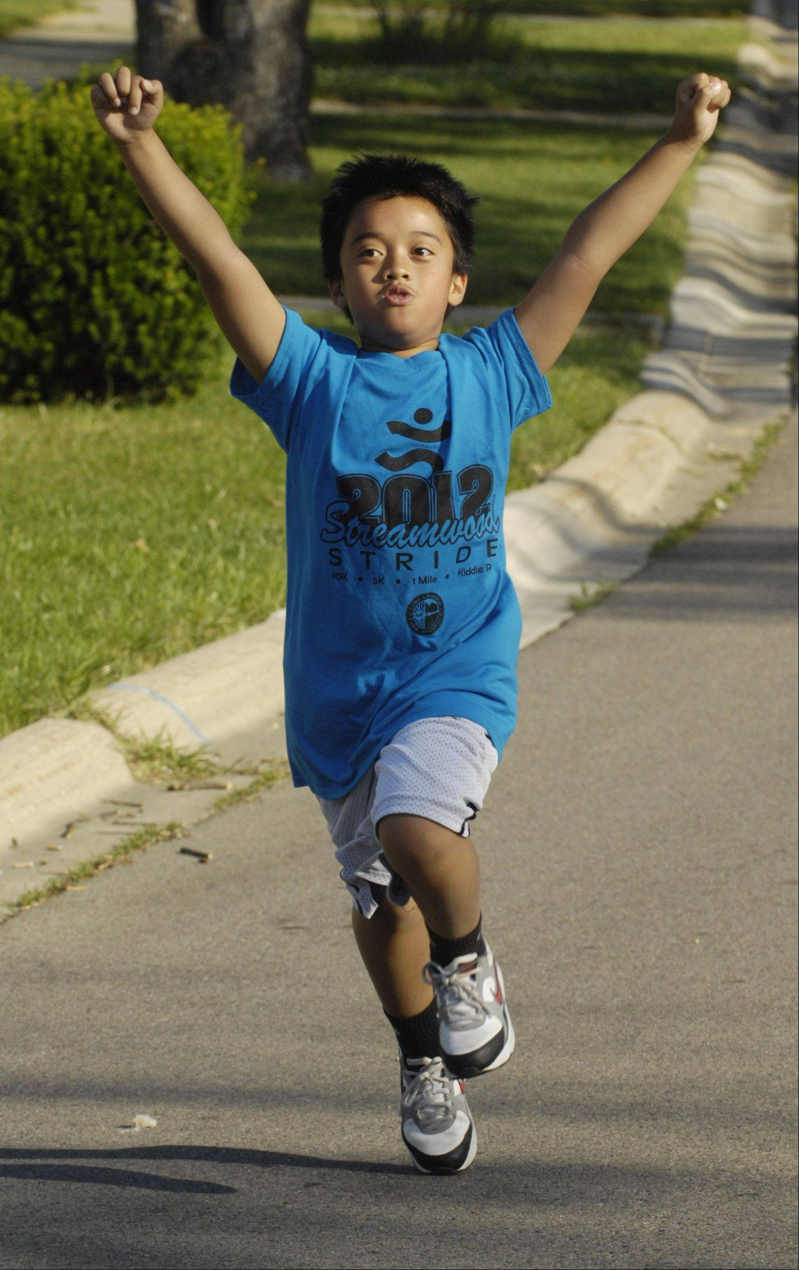 Though not the first runner across the finish line, Jericho Salas, 9, of Streamwood celebrates his completion of the one-mile fun run during the annual Streamwood Stride Saturday.