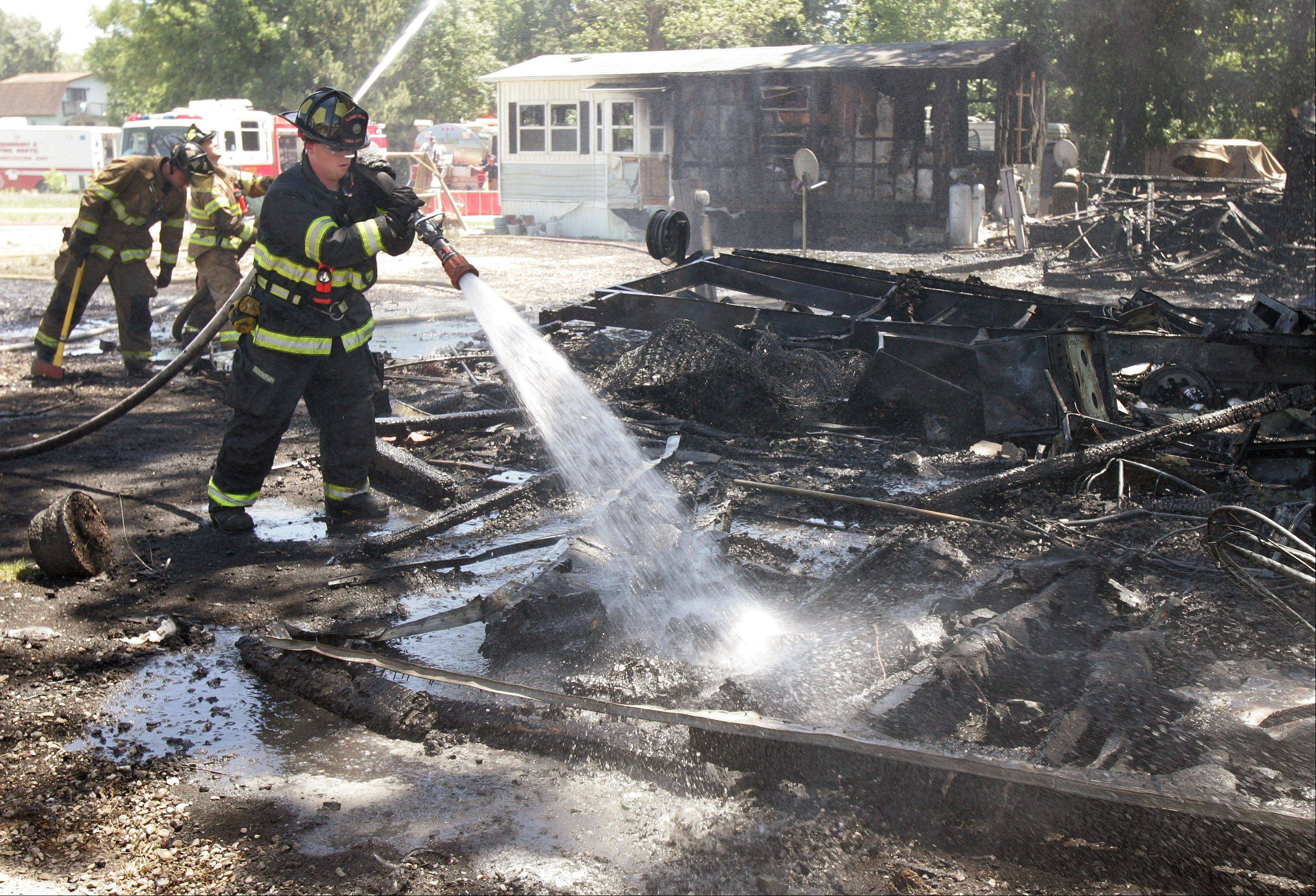 A Lake Villa firefighter sprays water on the remains of one mobile home as he joined other Lake County firefighters who battled a fire involving multiple mobile homes in Grass Lake Marina & R.V. Park Tuesday near Antioch. Fire departments from Antioch, Lake Villa, Fox Lake and Gurnee assisted in the multiple alarm fire.